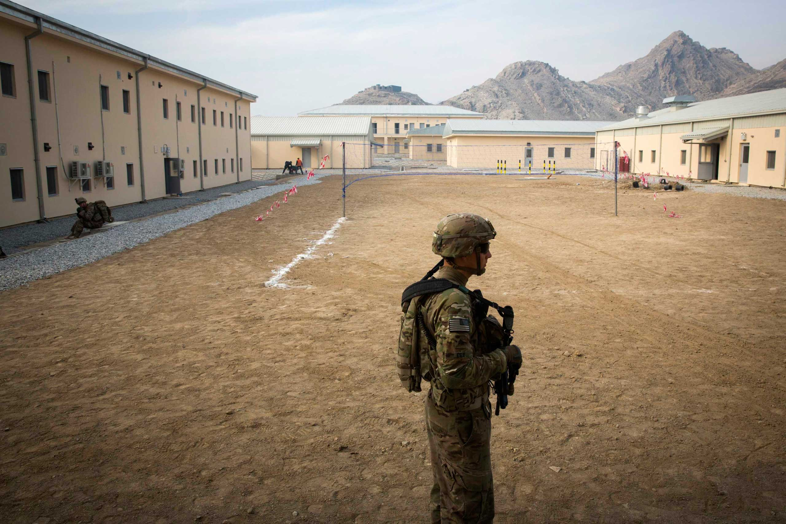 A U.S. soldier from the 3rd Cavalry Regiment walks through an Afghan police station near Jalalabad in the Nangarhar province of Afghanistan on Dec. 20, 2014.