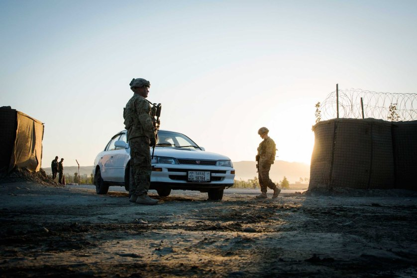 U.S. soldiers from 3rd Cavalry Regiment flag a car to stop to be screened for explosives near forward operating base Gamberi in the Laghman province of Afghanistan