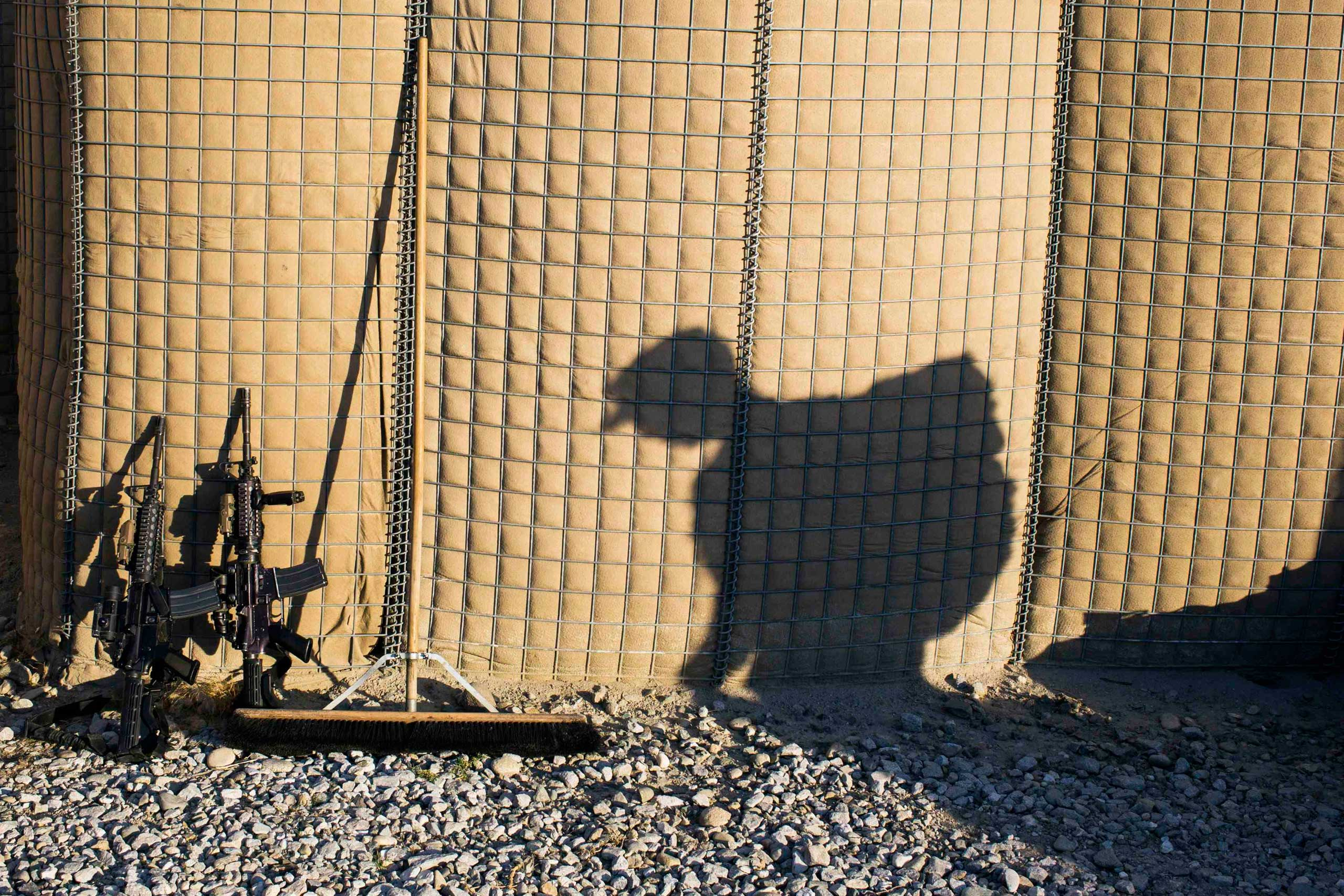 A U.S. soldier from D Troop of the 3rd Cavalry Regiment carries a backpack to a shipping container during preparations for leaving Afghanistan at forward operating base Gamberi in the Laghman province of Afghanistan on Dec. 28, 2014.