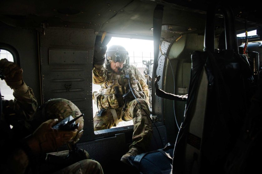 A crew member climbs into a U.S. Blackhawk helicopter before it takes off following a mission to take Brigadier General Christopher Bentley to inspect an Afghan National police installation in the Nangarhar province of Afghanistan