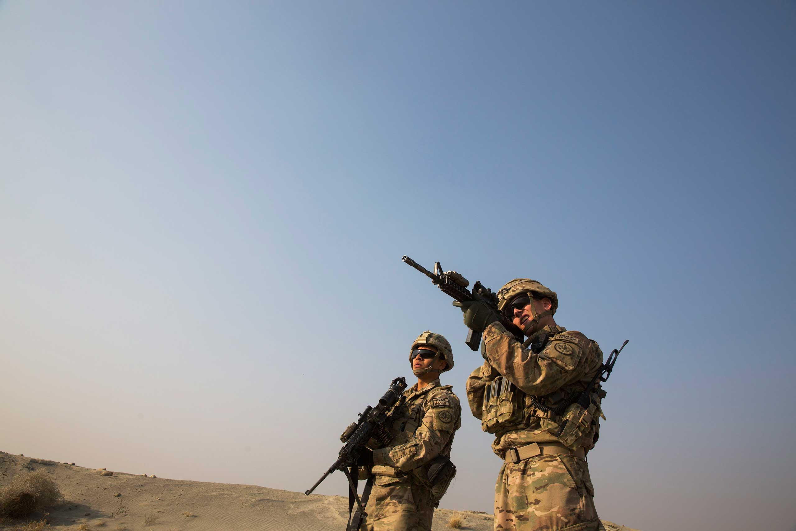 A U.S. soldier from the 3rd Cavalry Regiment uses the optic on his rifle to observe Afghans in the distance, near forward operating base Gamberi, in the Laghman province of Afghanistan, Dec. 15, 2014.