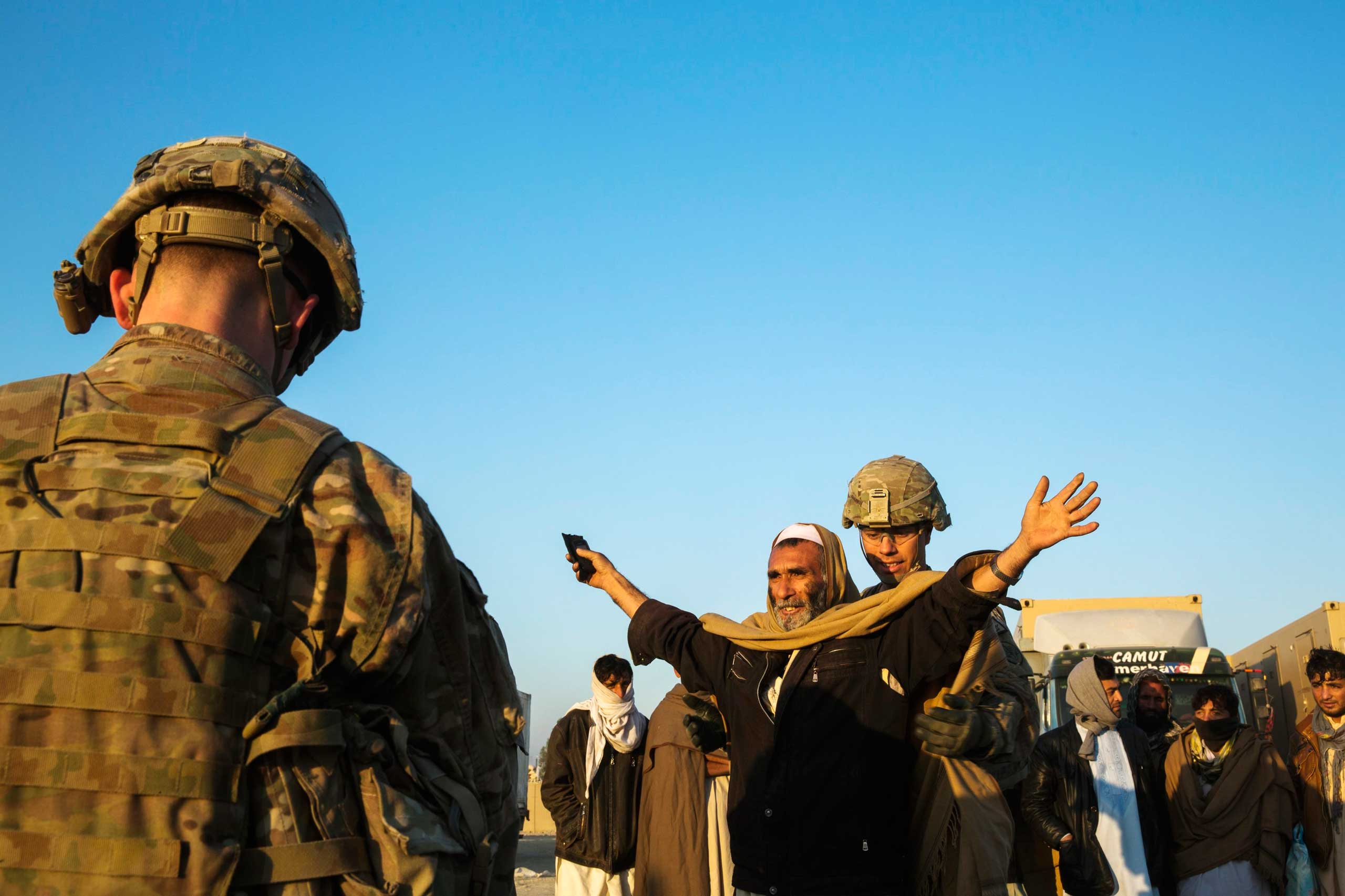 U.S. soldiers from the 3rd Cavalry Regiment interact with men selected to be biometrically screened near forward operating base Gamberi in the Laghman province of Afghanistan on Dec. 14, 2014.