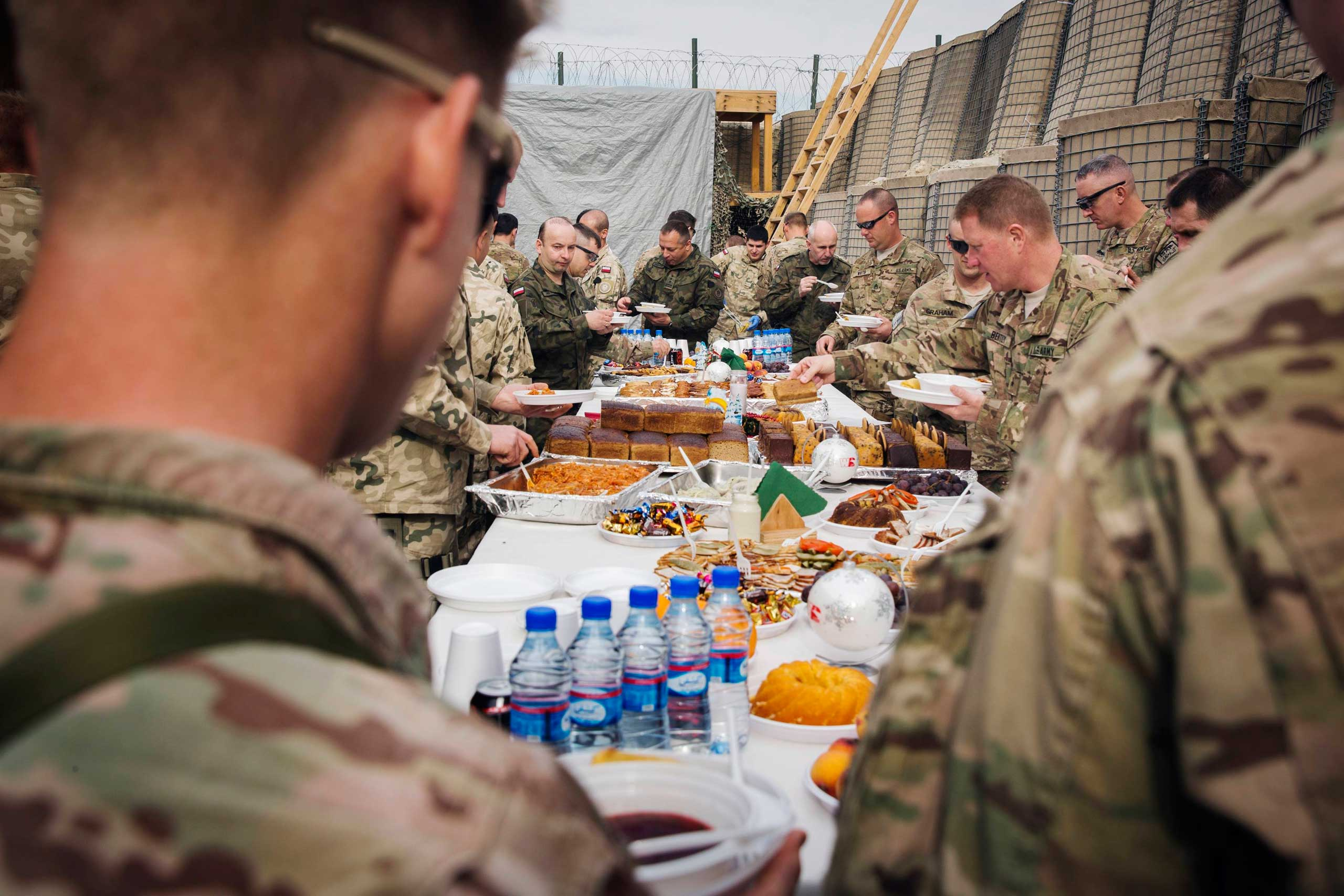 Brigadier General Christopher Bentley (2nd R) and U.S. soldiers from the 3rd Cavalry Regiment take part in a Christmas Eve celebration on forward operating base Gamberi in the Laghman province of Afghanistan on Dec. 24, 2014.