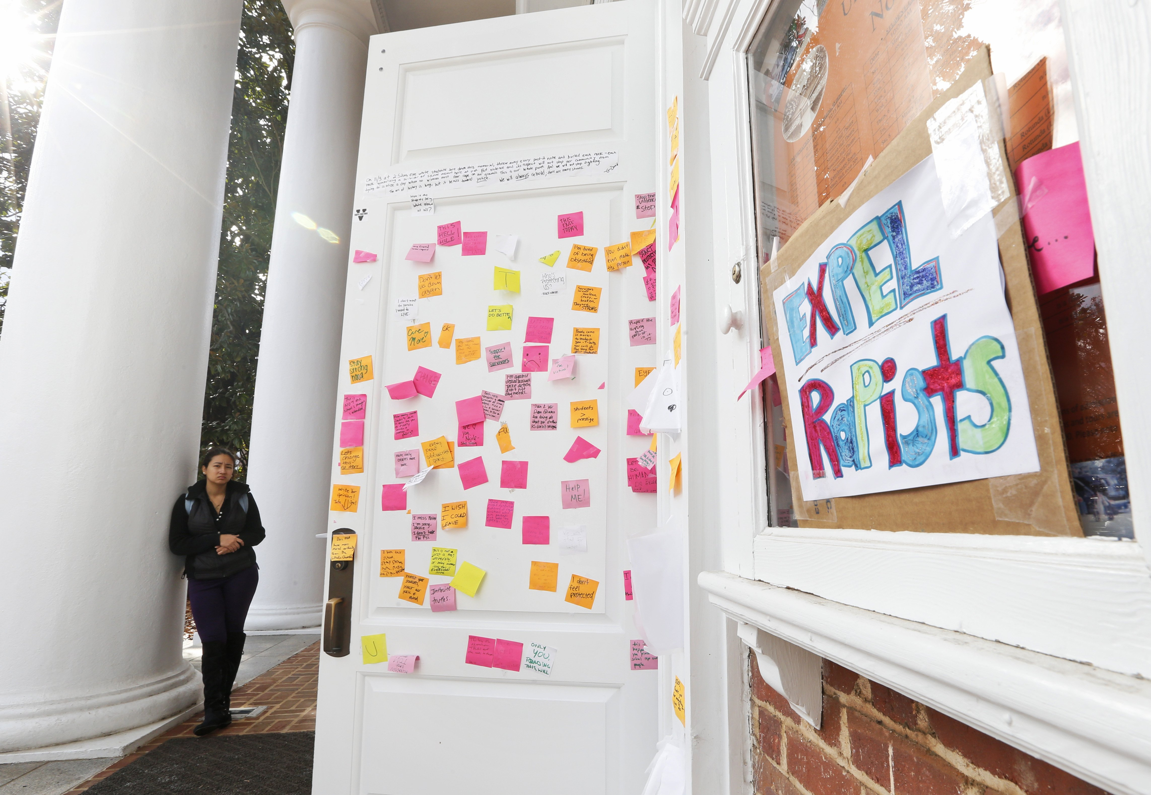A University of Virginia student looks over postings on the door of Peabody Hall related to the Phi Kappa Psi gang-rape allegations at the school in Charlottesville, Va., on Nov. 24, 2014