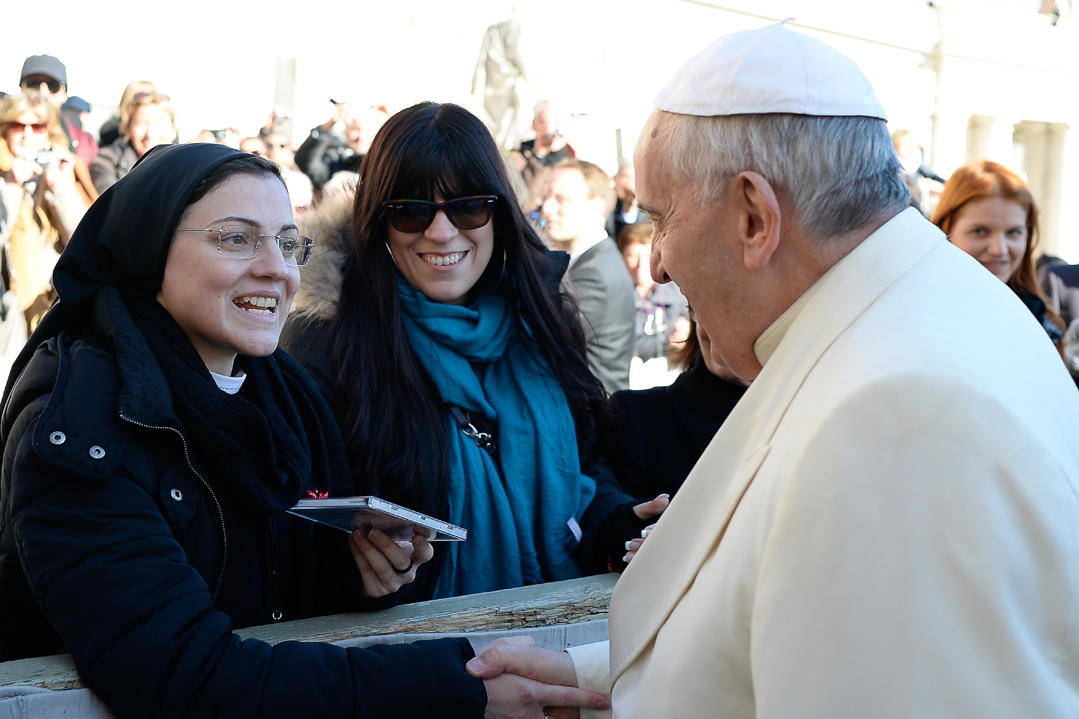 In this photo provided by the Vatican newspaper L' Osservatore Romano, Pope Francis greets Sister Cristina Scuccia as she presents him with her CD at the end of his weekly general audience in St. Peter's Square at the Vatican on Dec. 10, 2014