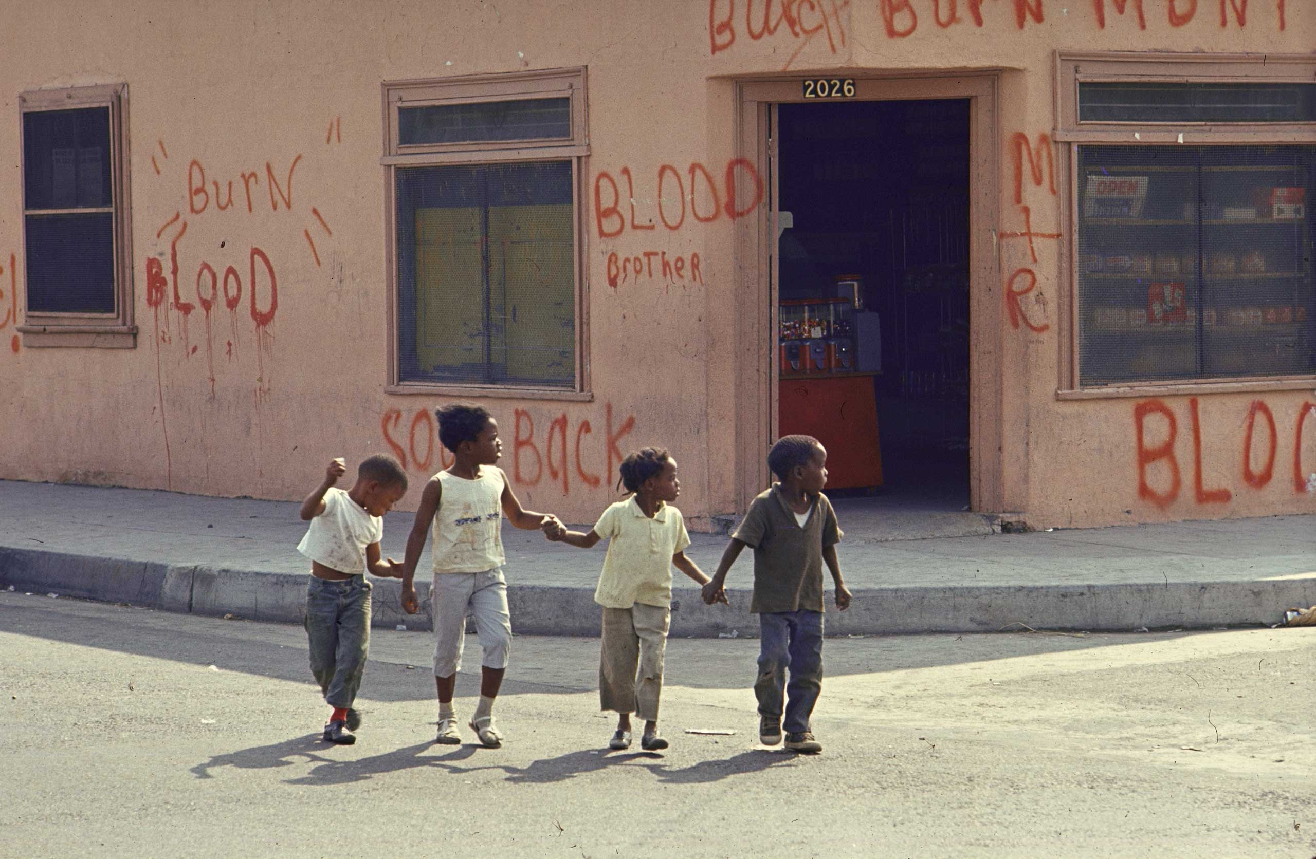 """<b>Caption from LIFE.</b> """"Children in Watts grow up with the signs of fear, desperation and hatred all around. The words painted last August on this little grocery store, telling rioters that it is owned by a Negro and urging them to burn something else, were left on the walls for months afterwards -- just in case."""""""