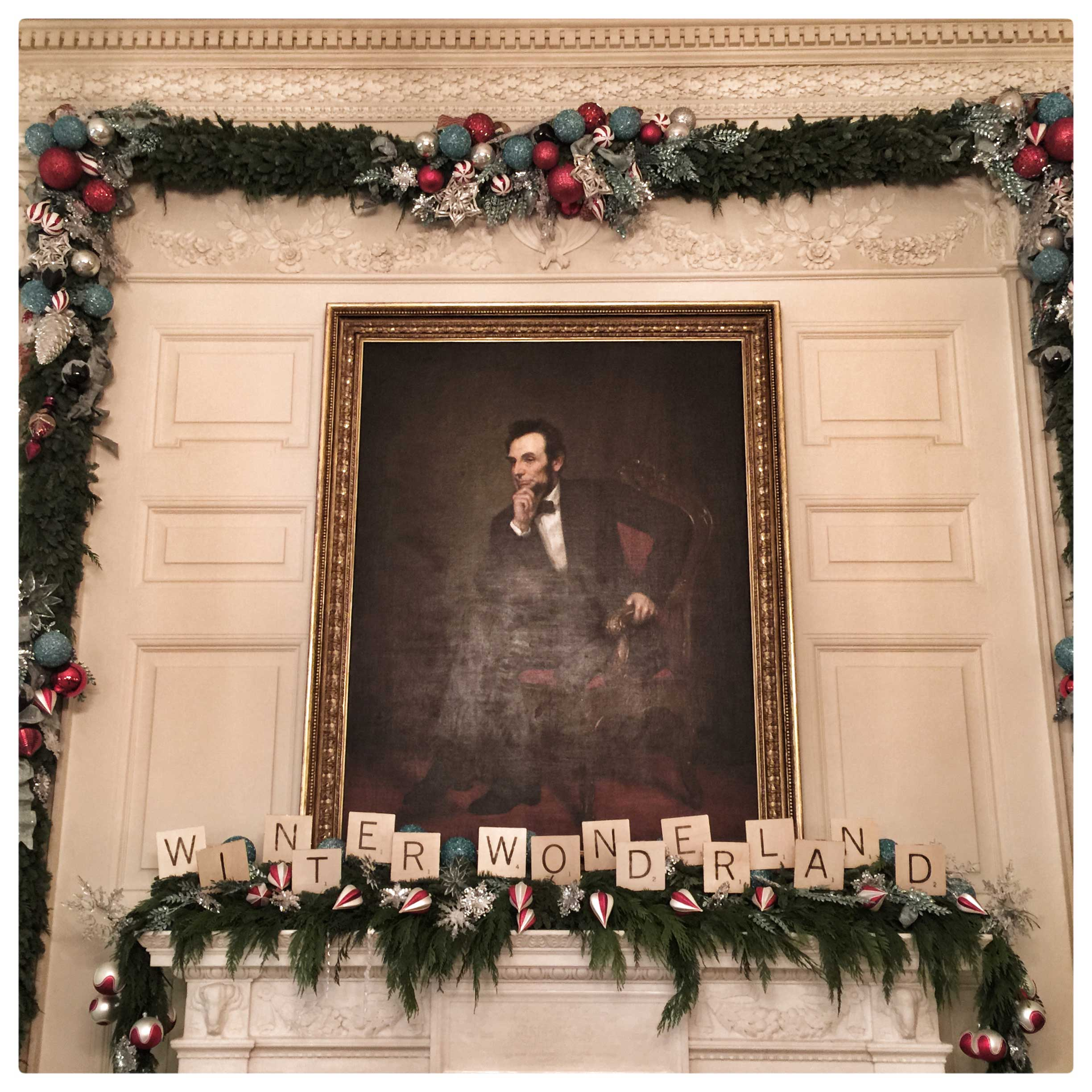 A portrait of President Lincoln in the State Dining Room at the White House is surrounded by holiday decorations.