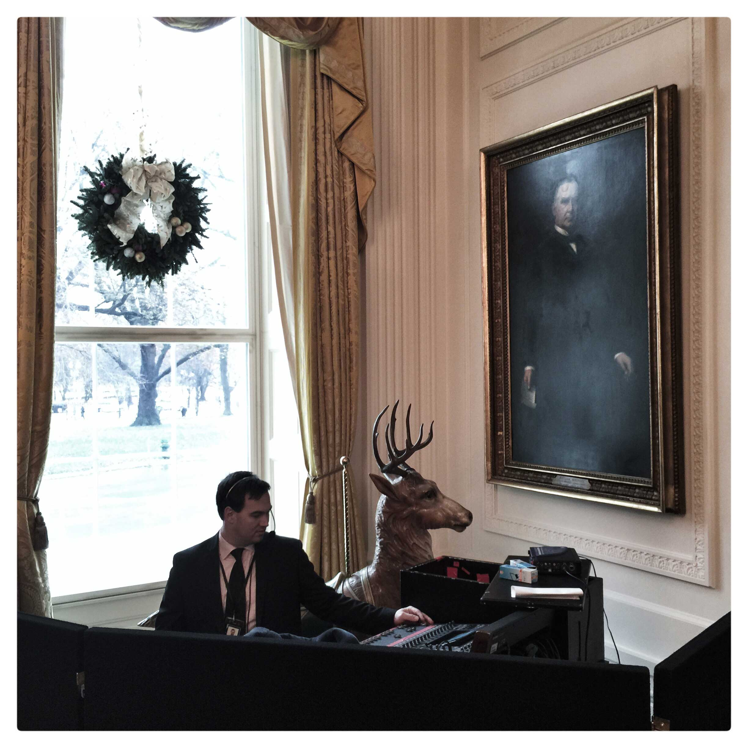 A sound technician works amongst holiday decorations at the White House.