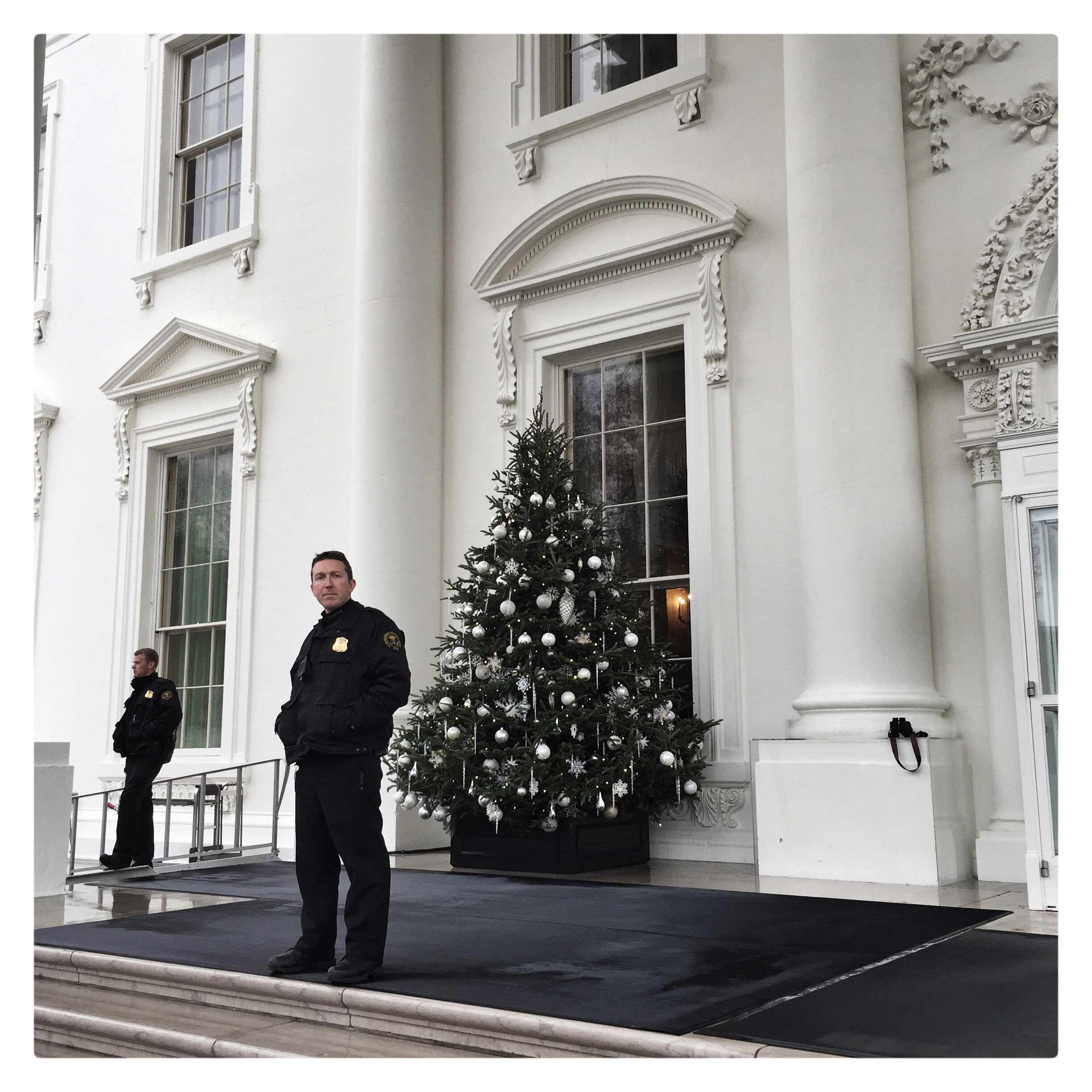 Secret Service agents stand in front of a Christmas tree at the North Portico of the White House.