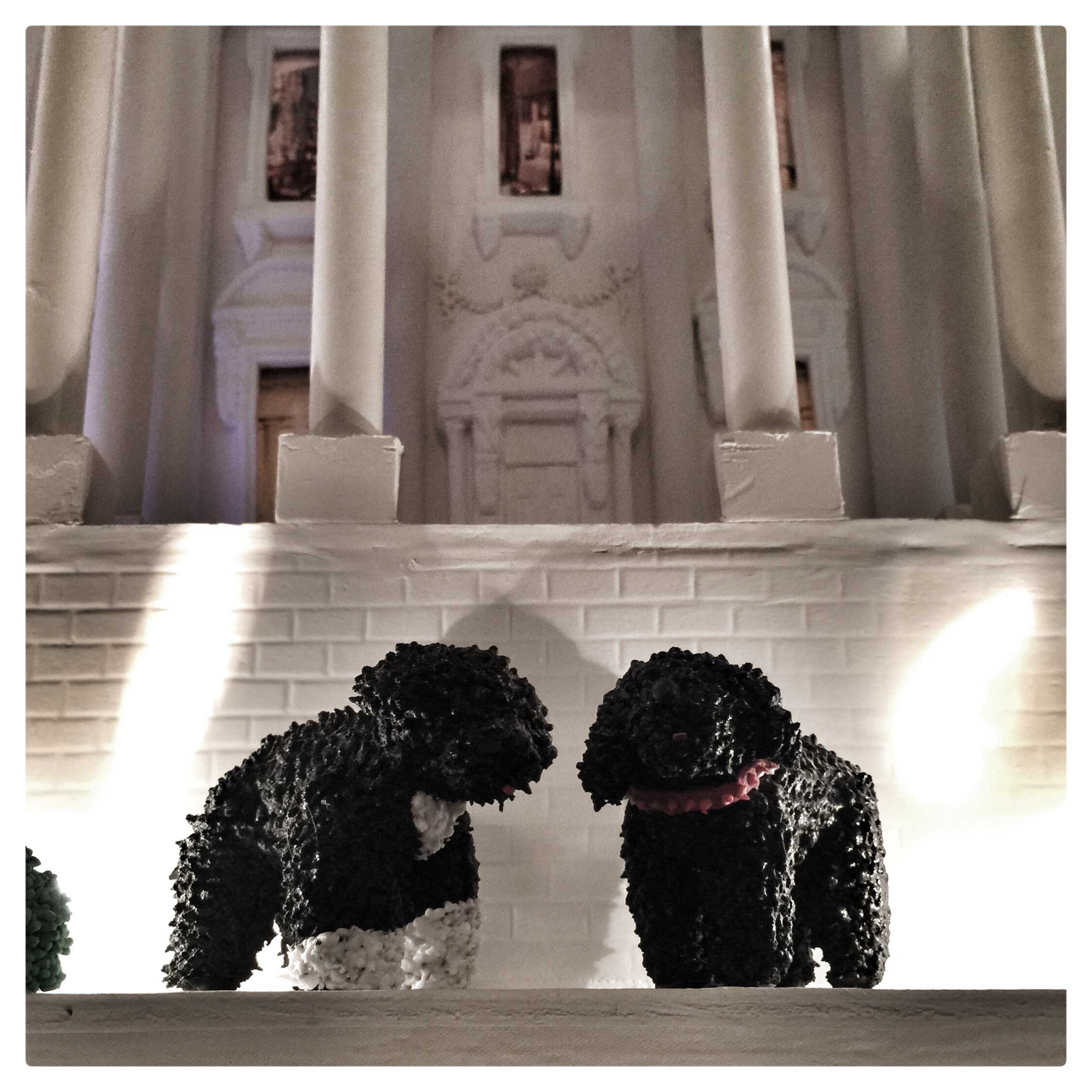 Figures of the Obama's two dogs in front of a gingerbread White House, as part of the holiday decorations at the WHite House.