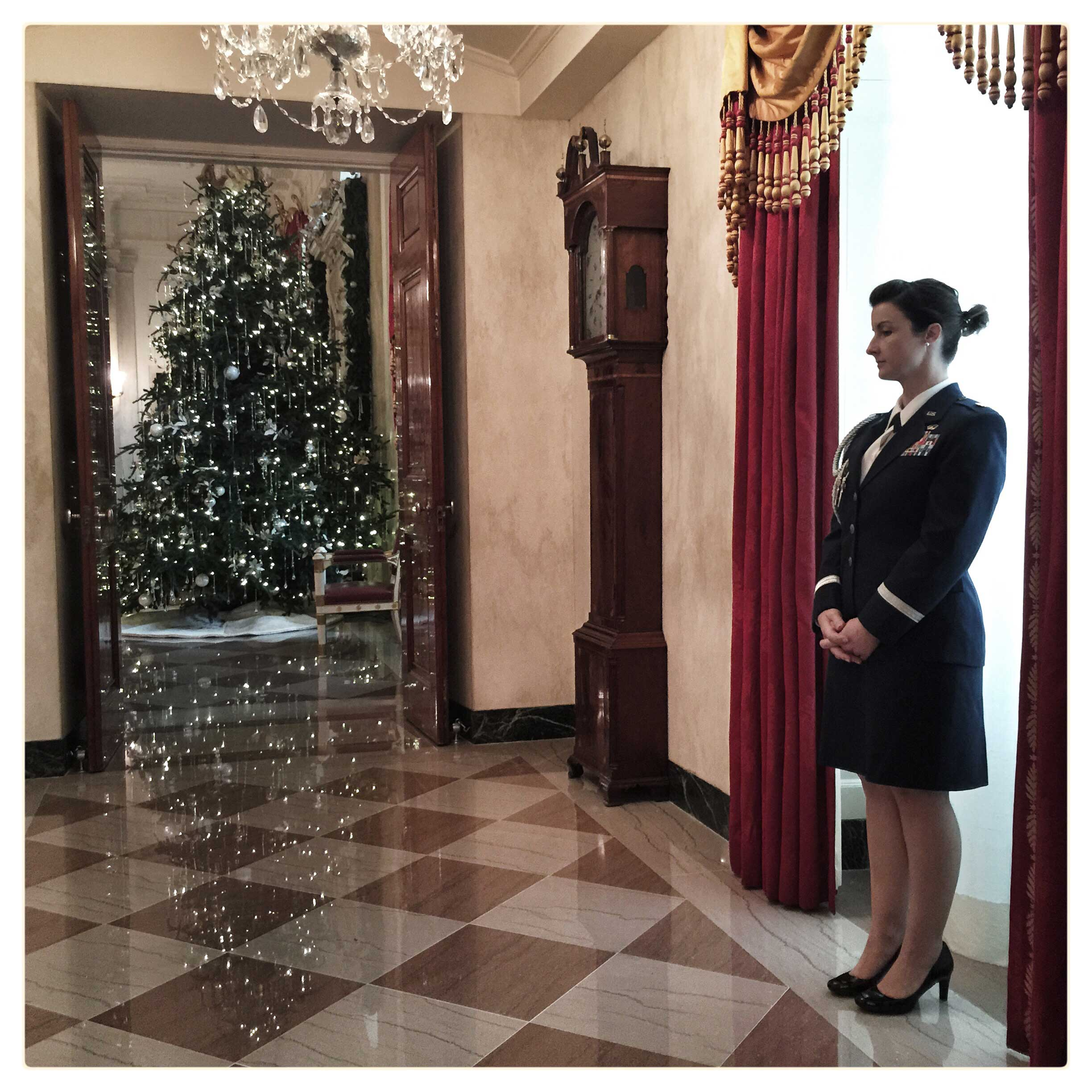 A member of the military stands near holiday decorations at the White House.