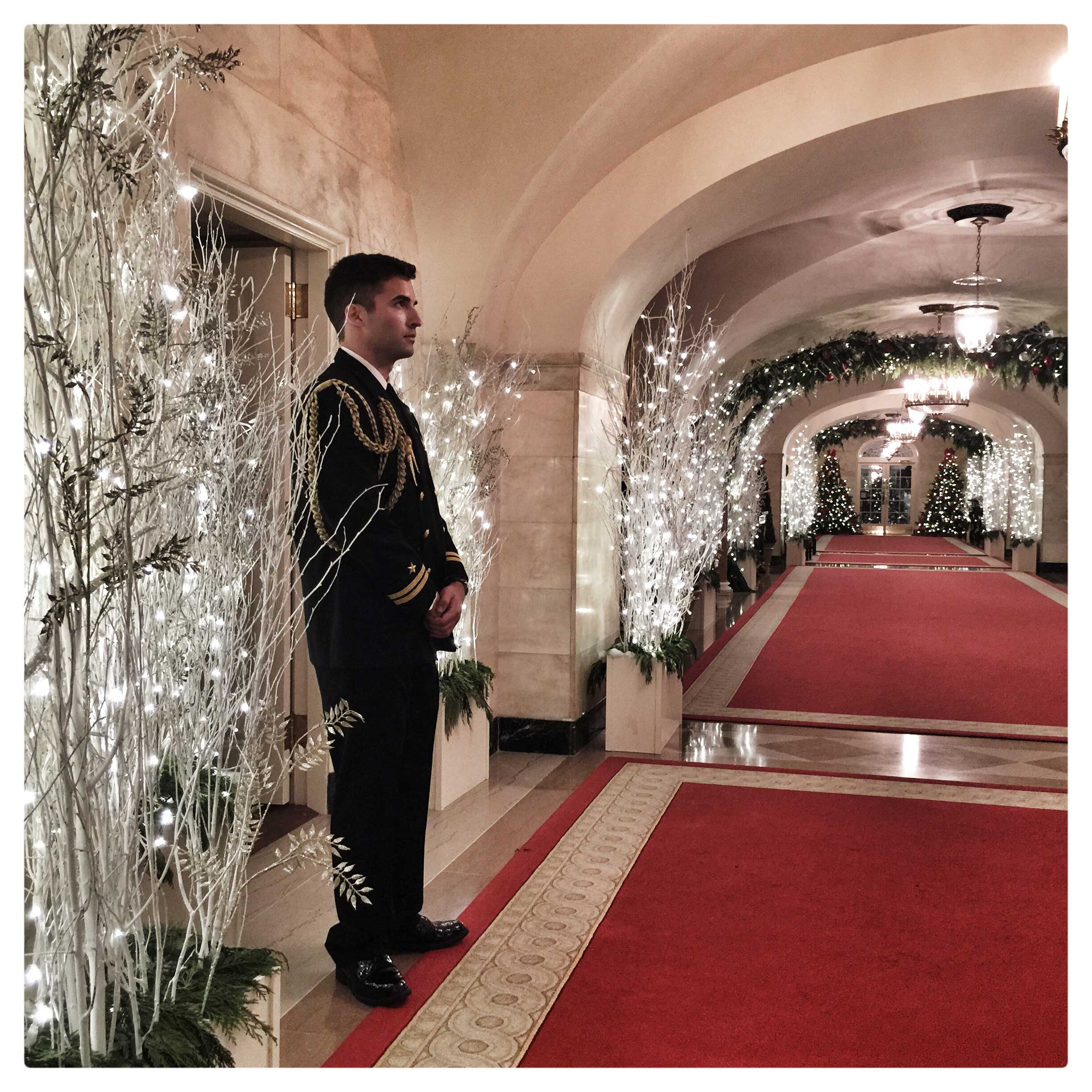 A military officer stands near holiday lights decorating a hallway in the White House.
