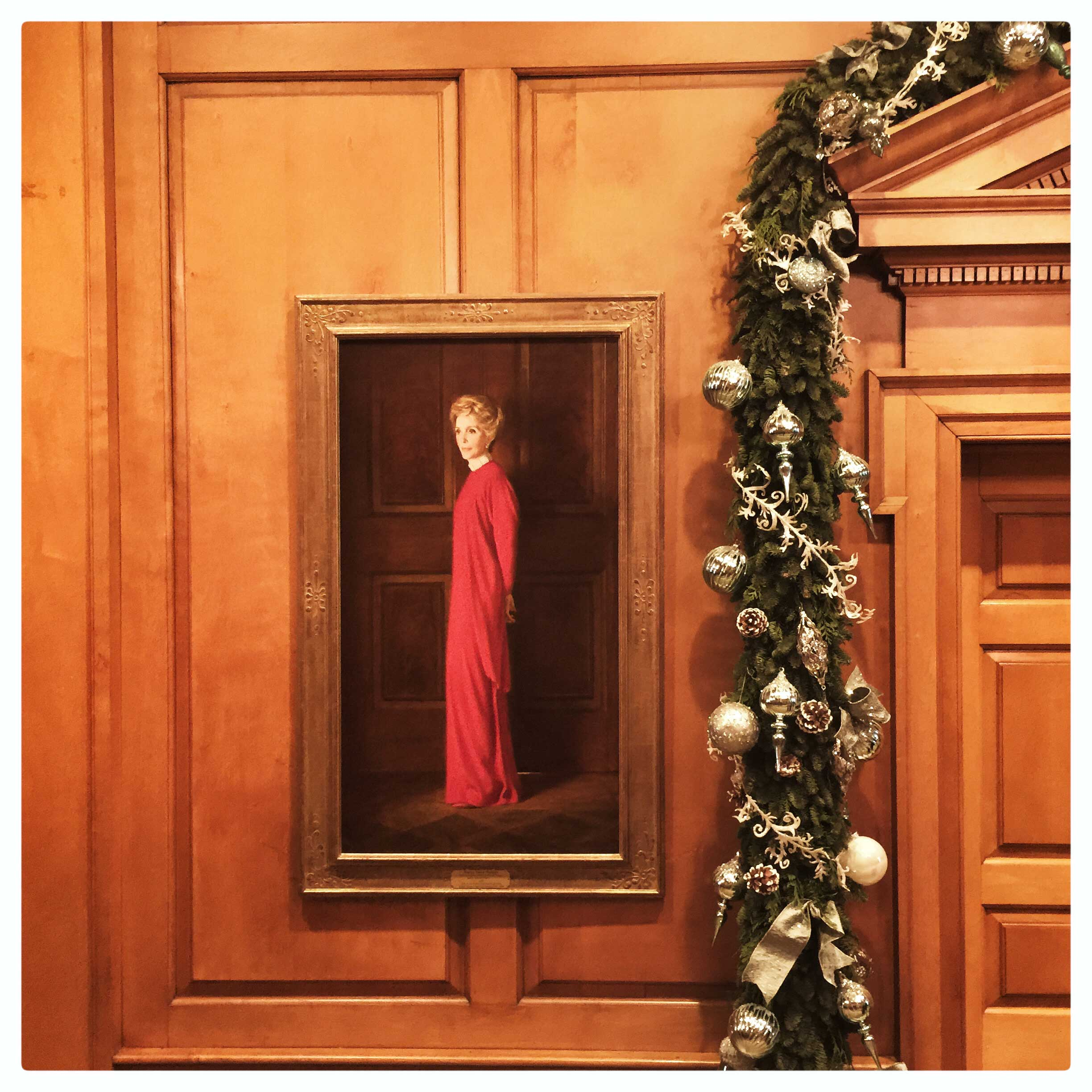 A portrait of former first lady Nancy Reagan next to holiday decorations in the East Wing of the White House.