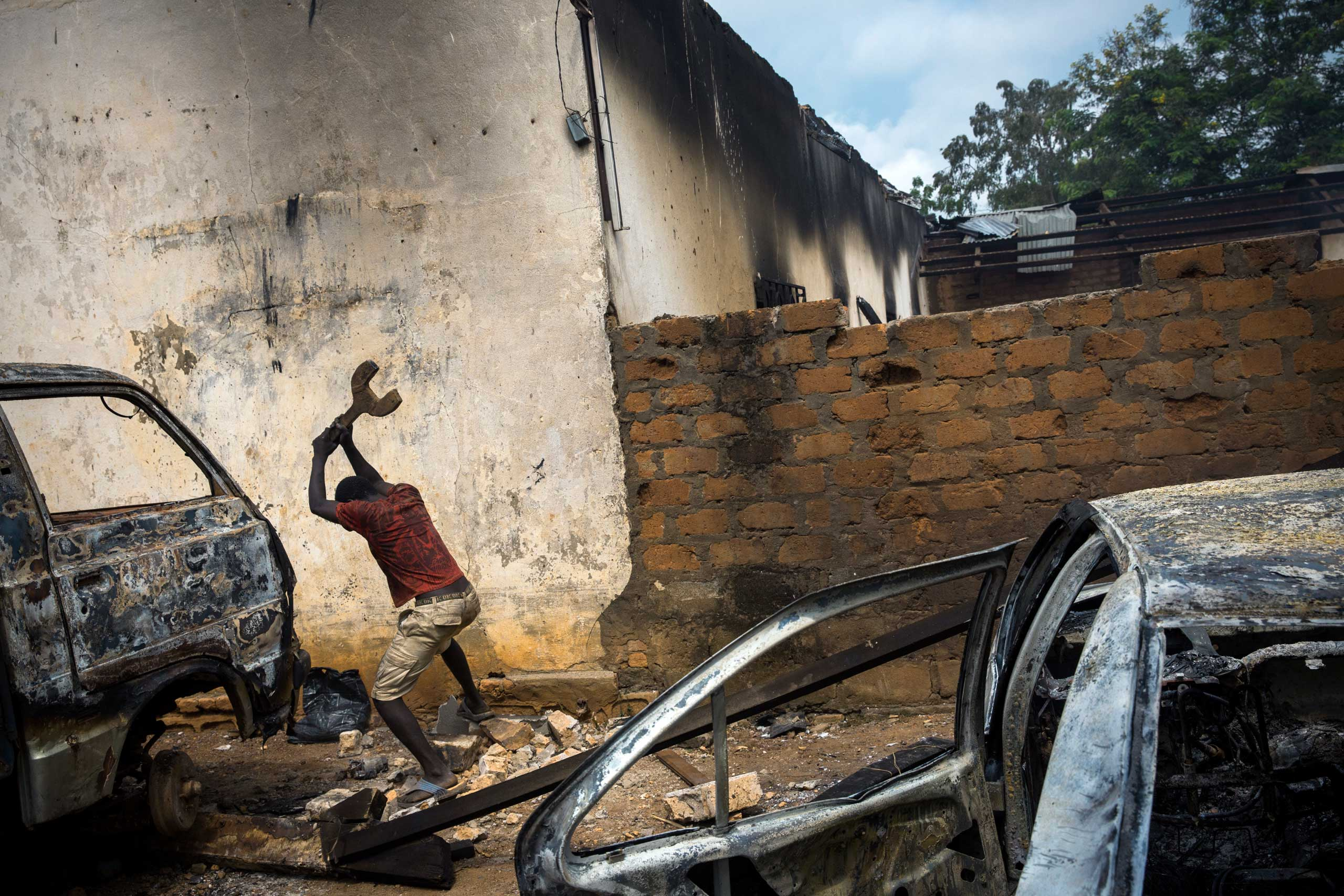 A Christian man destroys burnt out cars in rage, next to a looted mosque that had been set ablaze. Bangui, Central African Republic. Dec. 10, 2013.