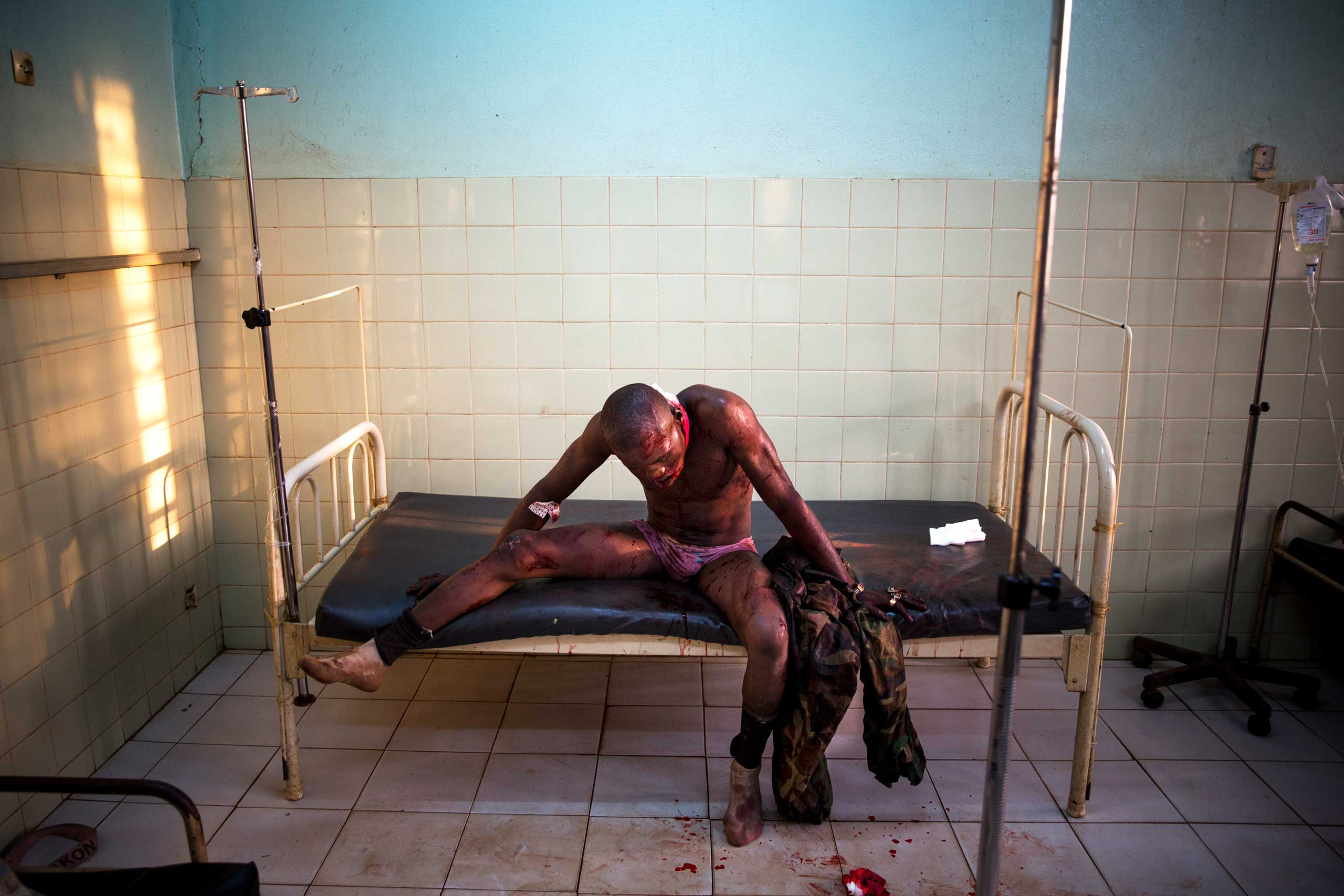 A soldier from the national army, wounded in fighting with Séléka rebels, waits to be treated at the Community Hospital. Bangui, Central African Republic. Jan. 31, 2014.
