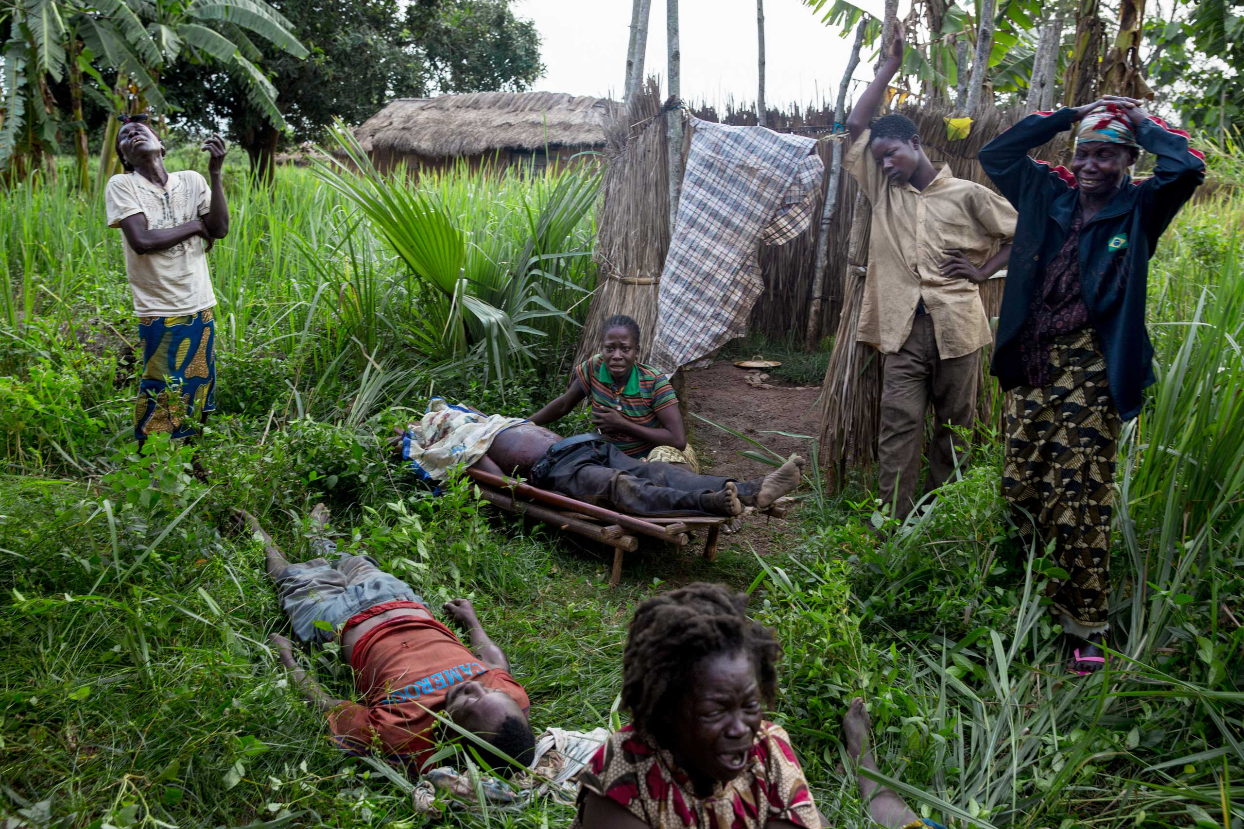 """Relatives mourn the death of two men and one woman who had just been slaughtered amid accusations they were anti-balaka. The woman was killed as  collateral damage"""" according to a Séléka colonel who admitted the killing. Gulinga, Central African Republic. April 14, 2014."""