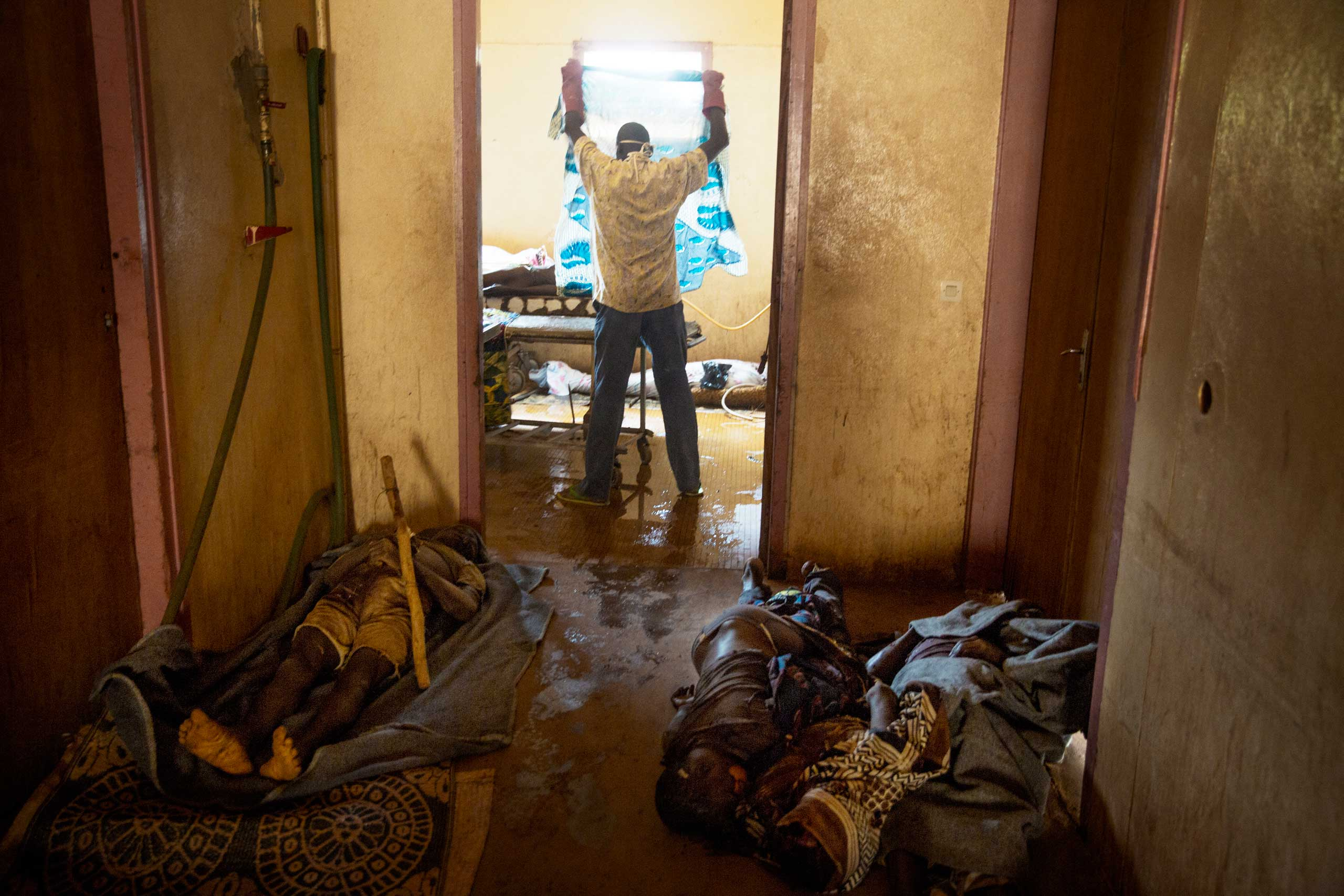 A morgue workers prepares a body for funeral after a deadly bout of street violence between Séléka and anti-balaka. Bangui, Central African Republic. Dec. 16, 2013.