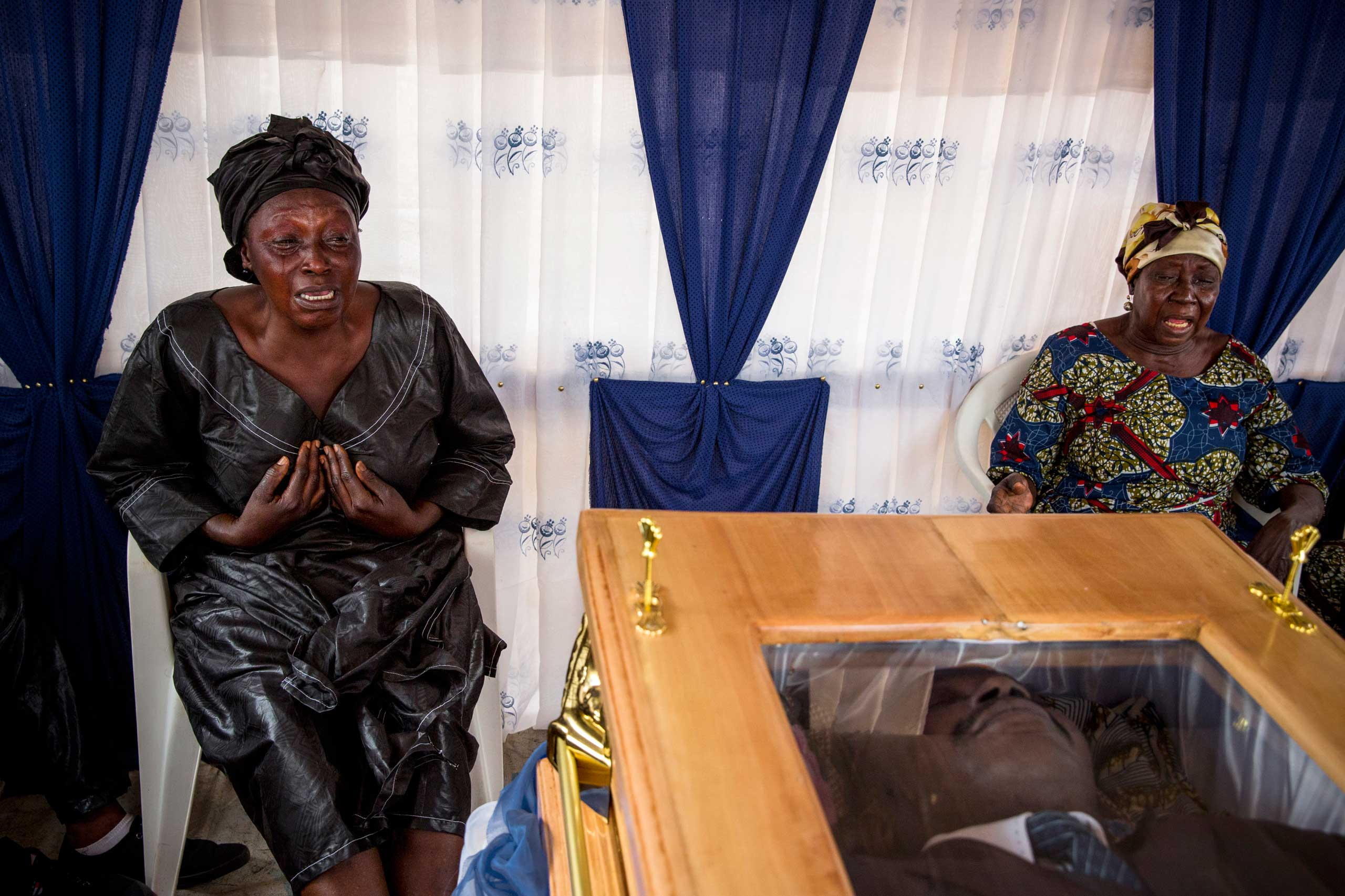 Relatives attending a funeral touch the coffin of a judge who was said to be killed by Séléka fighters. Bangui, Central African Republic. Nov. 29, 2013.