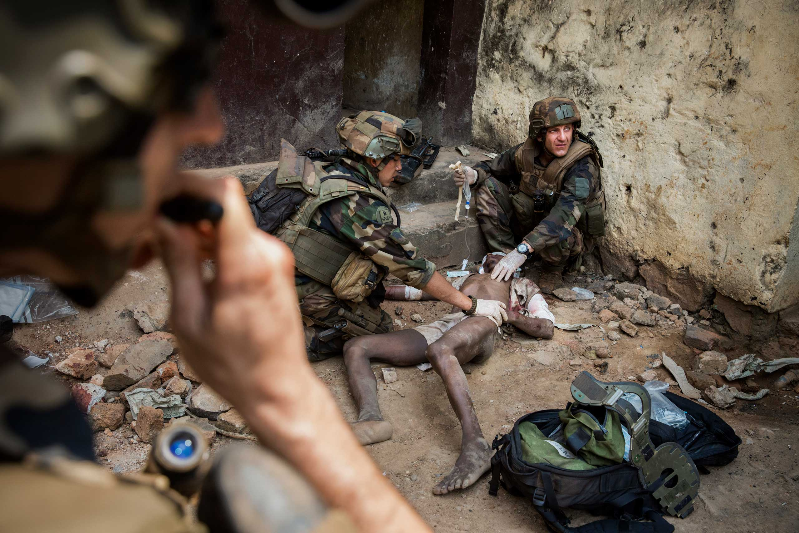 French troops attempt to save a Muslim man who was attacked by Christians while he was in jail, after having been accused of being a member of Séléka responsible for many executions. Bangui, Central African Republic. Jan. 22, 2014.