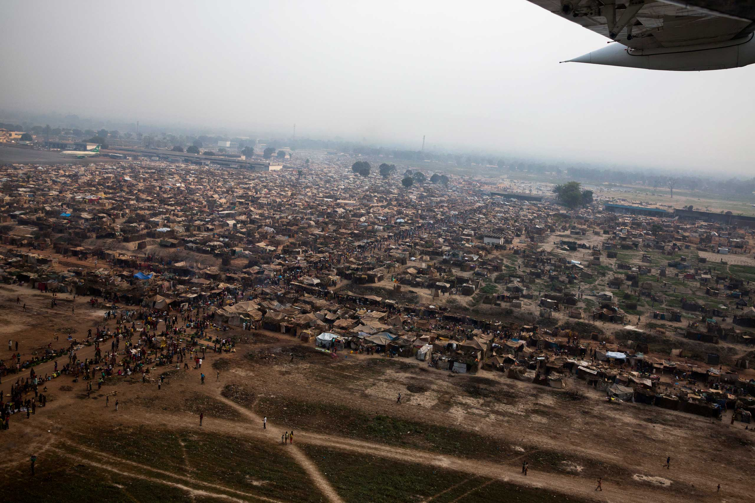 An overhead scene of the makeshift camp near Bangui's main airport that would grow to more than 100,000 people at its peak. They had fled fighting between Séléka and anti-balaka, and felt more secure with French forces at the entrance. Bangui, Central African Republic. Jan. 29, 2014.