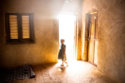 A young girls stands in the doorway of a house. A member of her family, 21 year old Fleuri Doumana, was killed two days earlier by a grenade launched by a member of Seleka. Bangui, Central African Republic.