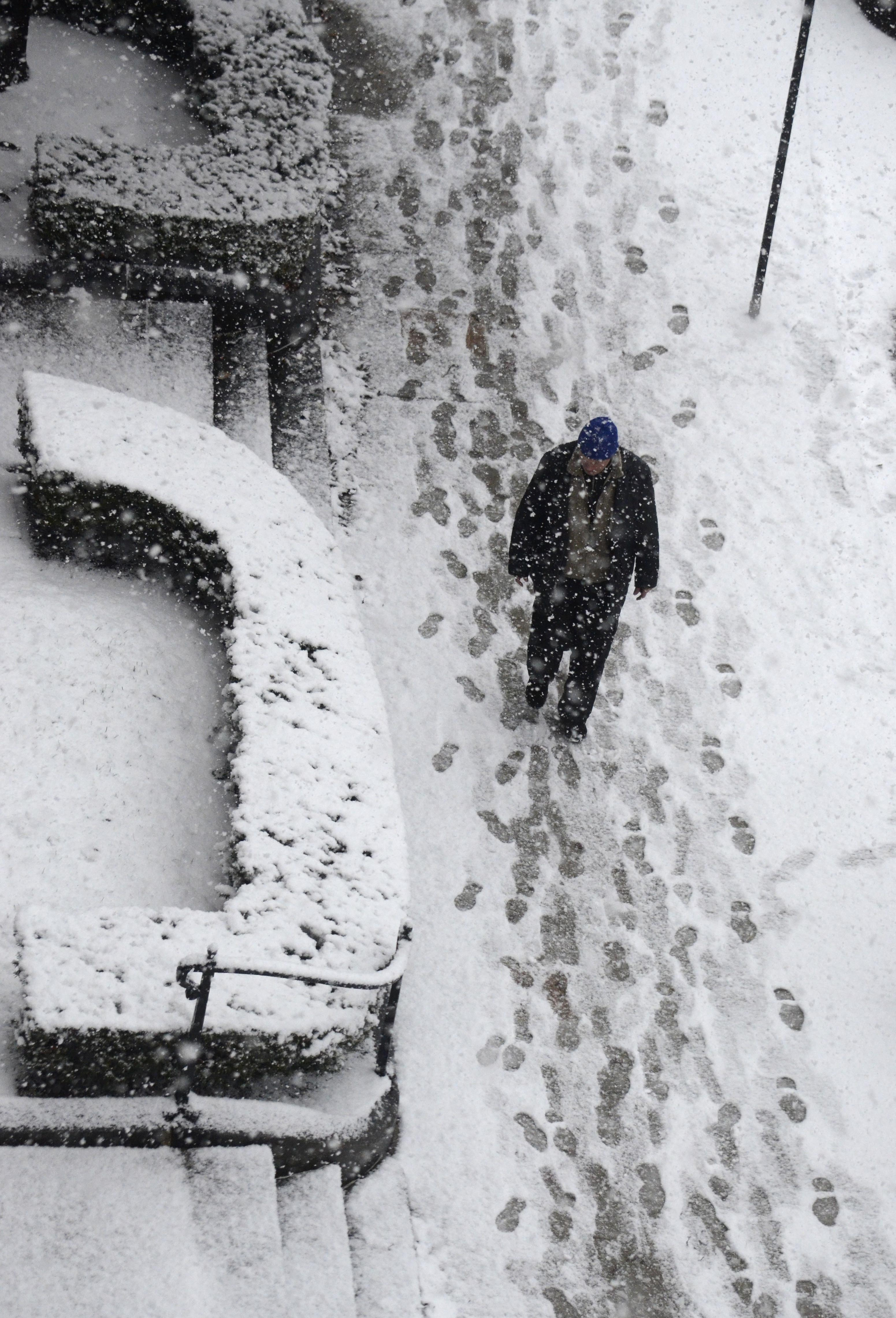 A man walks in snow in Pittsfield, Mass., as snow accumulates on the sidewalk on Dec. 10, 2014.