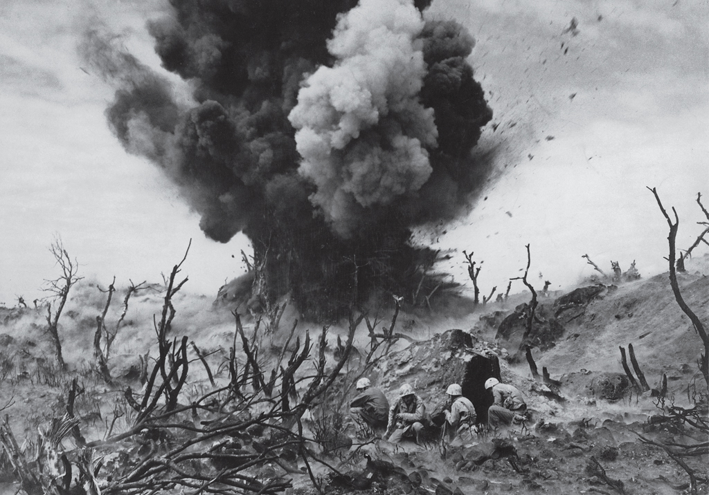 In a picture that captures the violence and sheer destruction inherent in war perhaps more graphically than any other ever published in LIFE, Marines take cover on an Iwo Jima hillside amid the burned-out remains of banyan jungle, as a Japanese bunker is obliterated in March 1945.