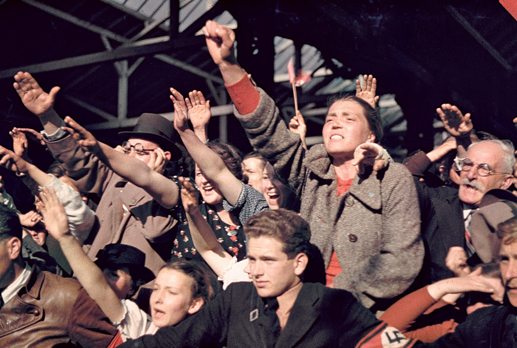 "Austrians cheer Adolf Hitler during his 1938 campaign to unite Austria and Germany. In the rapt faces, straining bodies, and adulation of the crowds swept up in Hitler's mad vision, one senses the eagerness of millions to forge a ""Thousand Year Reich"" at, literally, any cost."