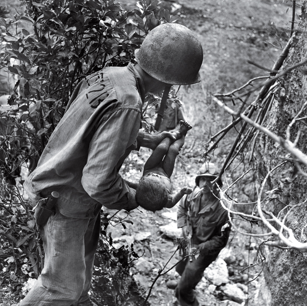 In a photo that somehow comprises both tenderness and horror, an American Marine cradles a near-dead infant pulled from under a rock while troops cleared Japanese fighters and civilians from caves on Saipan in the summer of 1944. The child was the only person found alive among hundreds of corpses in one cave.