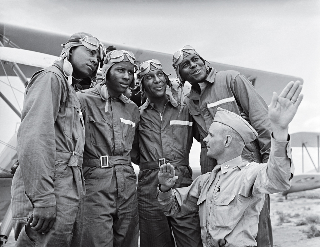 Members of the U.S. Army Air Corps' legendary 99th Pursuit Squadron, the Tuskegee Airmen, receive instruction about wind currents from a lieutenant in 1942. The Tuskegee fliers - the nation's first African American air squadron - served with distinction in the segregated American military.
