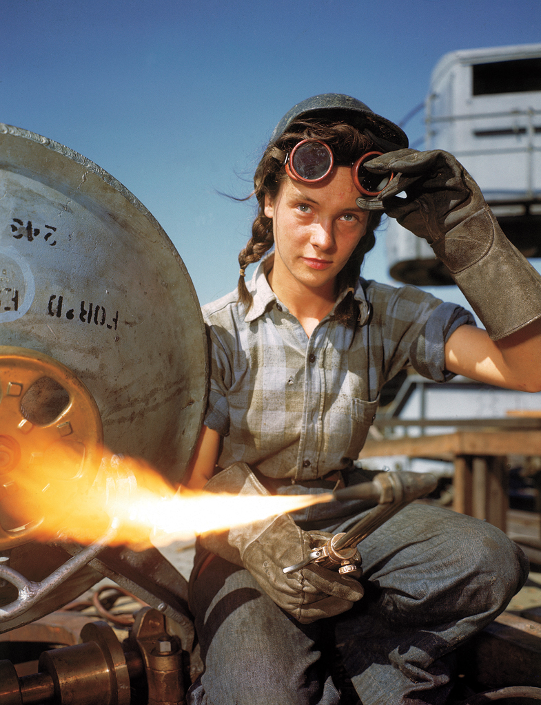 A welder at a boat-and-sub-building yard adjusts her goggles before resuming work, October, 1943. By 1945, women comprised well over a third of the civilian labor force (in 1940, it was closer to a quarter) and millions of those jobs were filled in factories: building bombers, manufacturing munitions, welding, drilling and riveting for the war effort.