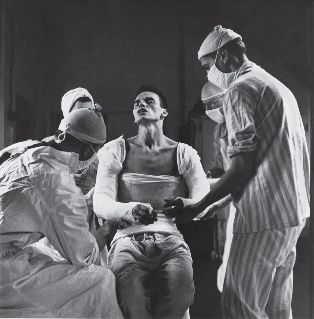 Army medic George Lott, wounded in both arms in November, 1944, grimaces as doctors mold a cast to his body. When Lott embarked on a 4,500-mile, seven-hospital journey of recovery, photographer Ralph Morse - astonished by the high level of medical care wounded troops received both at the front and behind the lines - traveled with him, and chronicled Lott's odyssey in a revelatory cover story for LIFE.