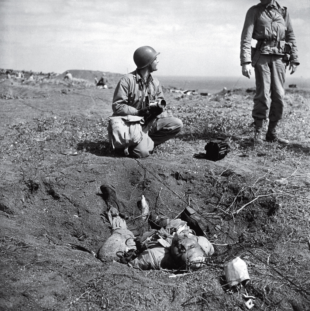 <b>Unpublished.</b> American troops chat near a dead Japanese soldier on Iwo Jima. The degree to which the Japanese were willing to fight to the death, rather than surrender, is summed up in one remarkable statistic: Close to 20,000 Japanese soldiers were killed during the battle; only around 200 were captured.
