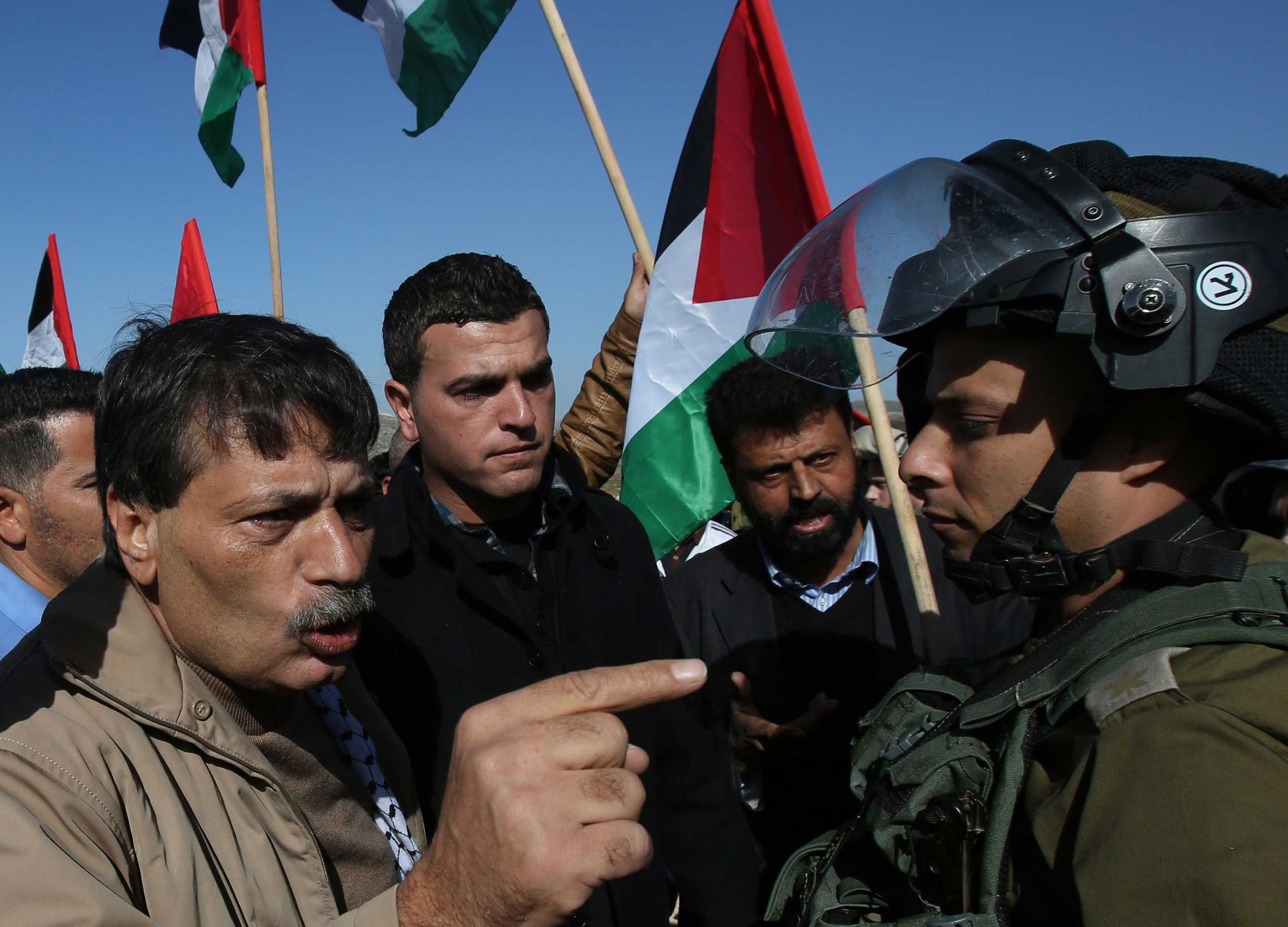 Palestinian official Ziad Abu Ein, in charge of the issue of Israeli settlements for the Palestinian Authority, argues with Israeli soldiers during a demonstration in the village of  Turmus Aya near Ramallah, on Dec. 10, 2014.
