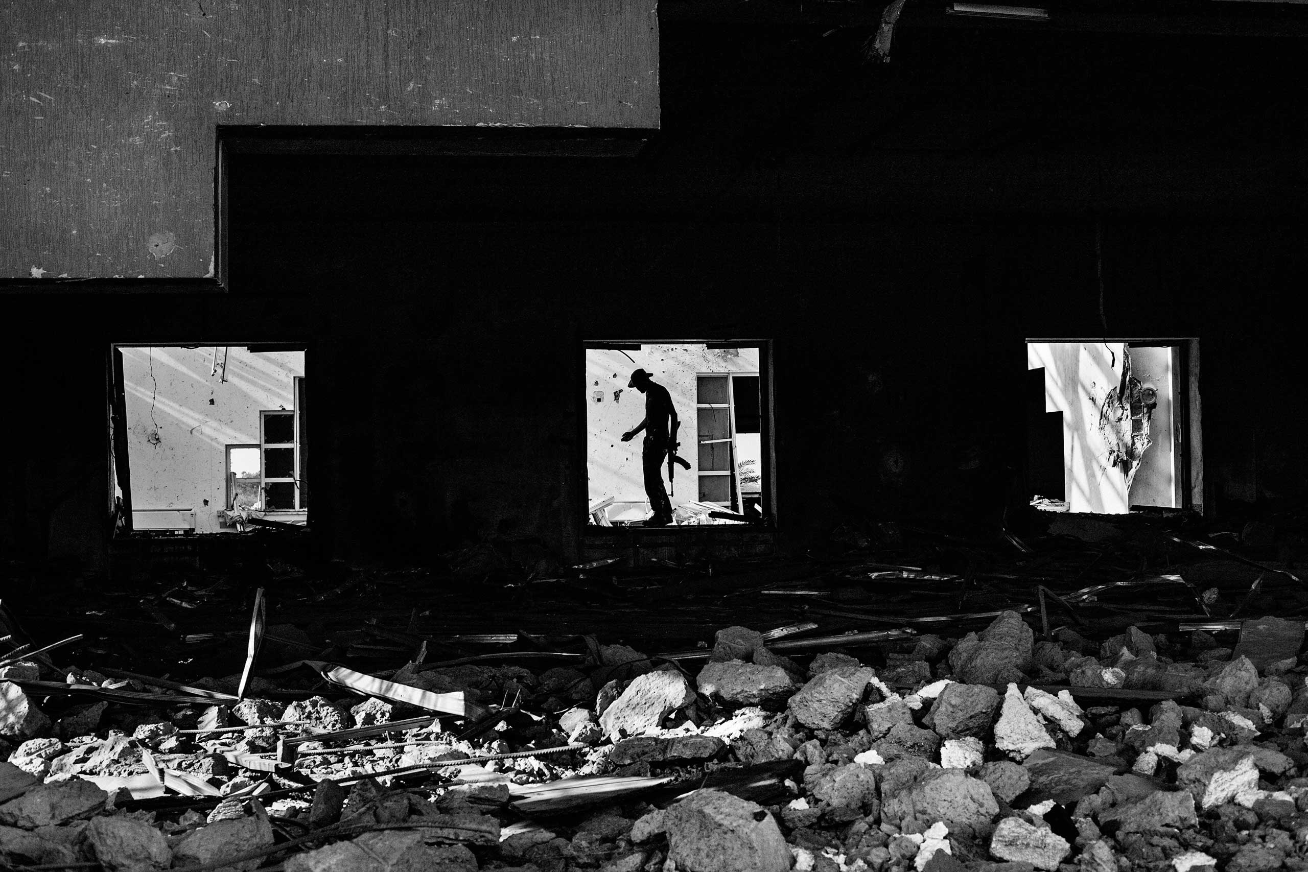 Libyan rebels during mopping up operation in a destroyed house in the outskirts of Sirte on October 20, 2011. The battle for Gaddafi's hometown was the last of the conflict. The rebels first captured Ougadougu and then entered Sirte. After nearly a month of fighting they conquered the city and, with the help of NATO bombing, capturing and killed Muammar Gaddafi.