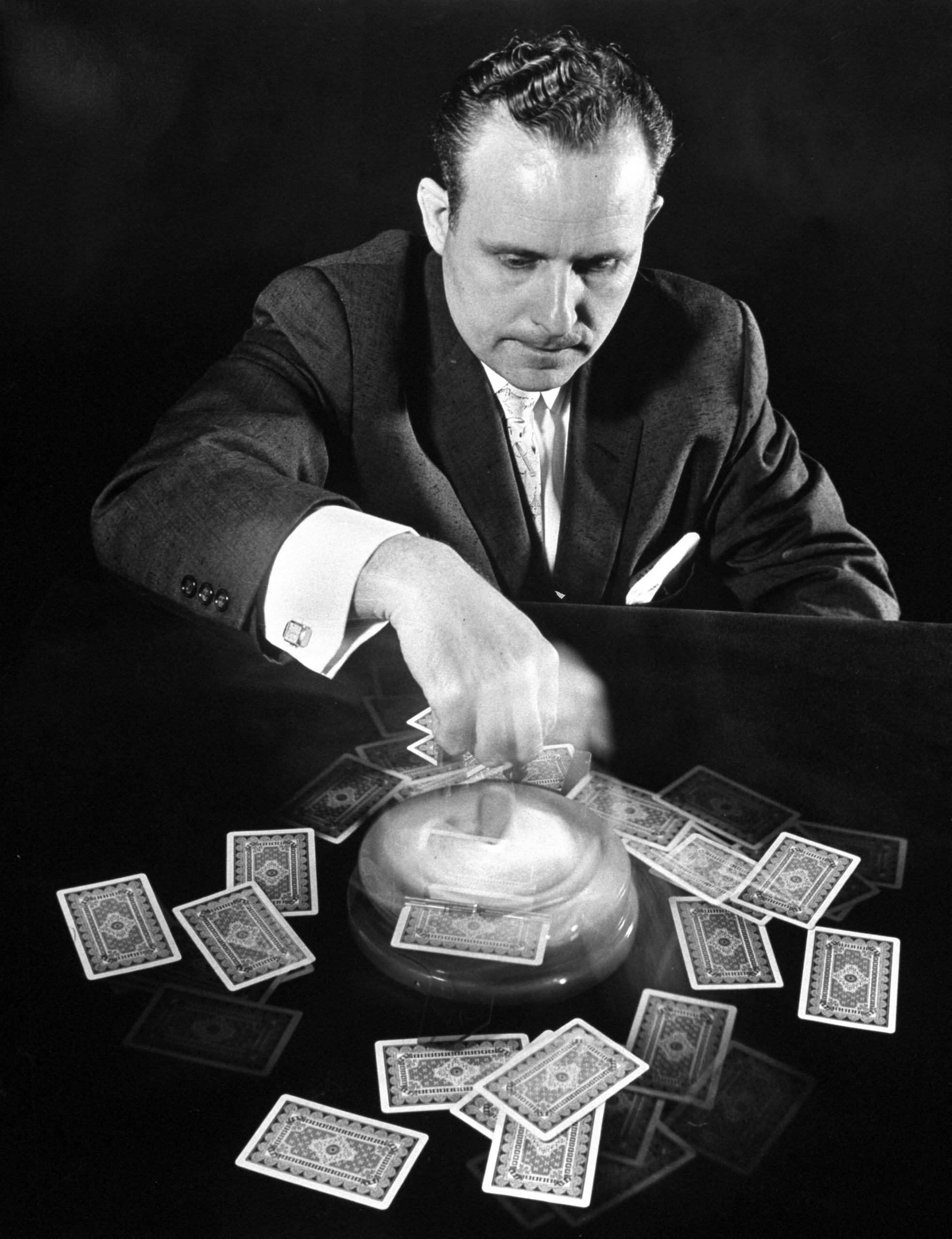 <b>Caption from LIFE.</b> Frank Wirth spins device that deals four card hands at once.