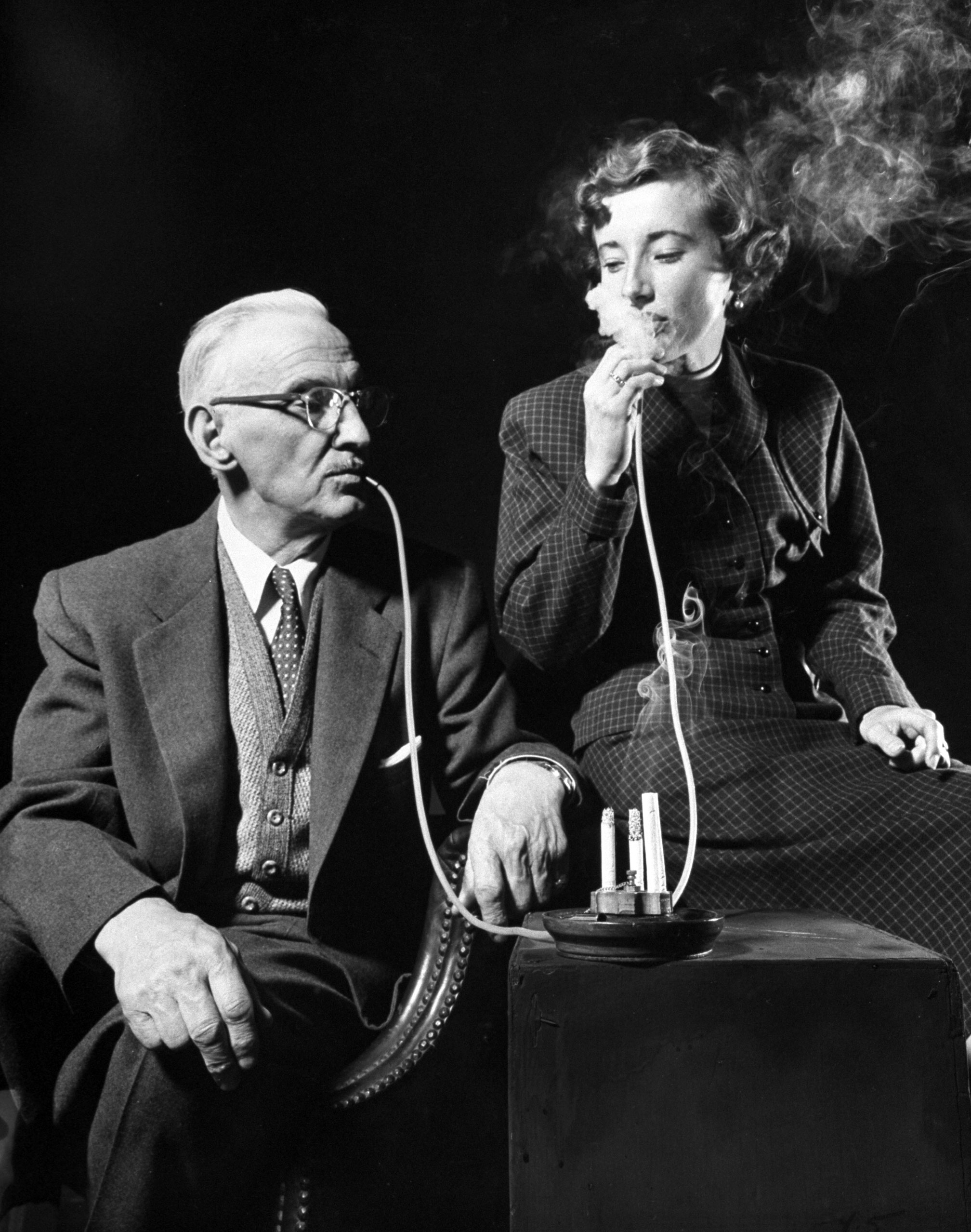 <b>Caption from LIFE.</b> Remote smoker to be placed at the bedside is demonstrated by Anton Widrich of Eatontown, N.J. and his granddaughter, Helen. Base catches ashes.