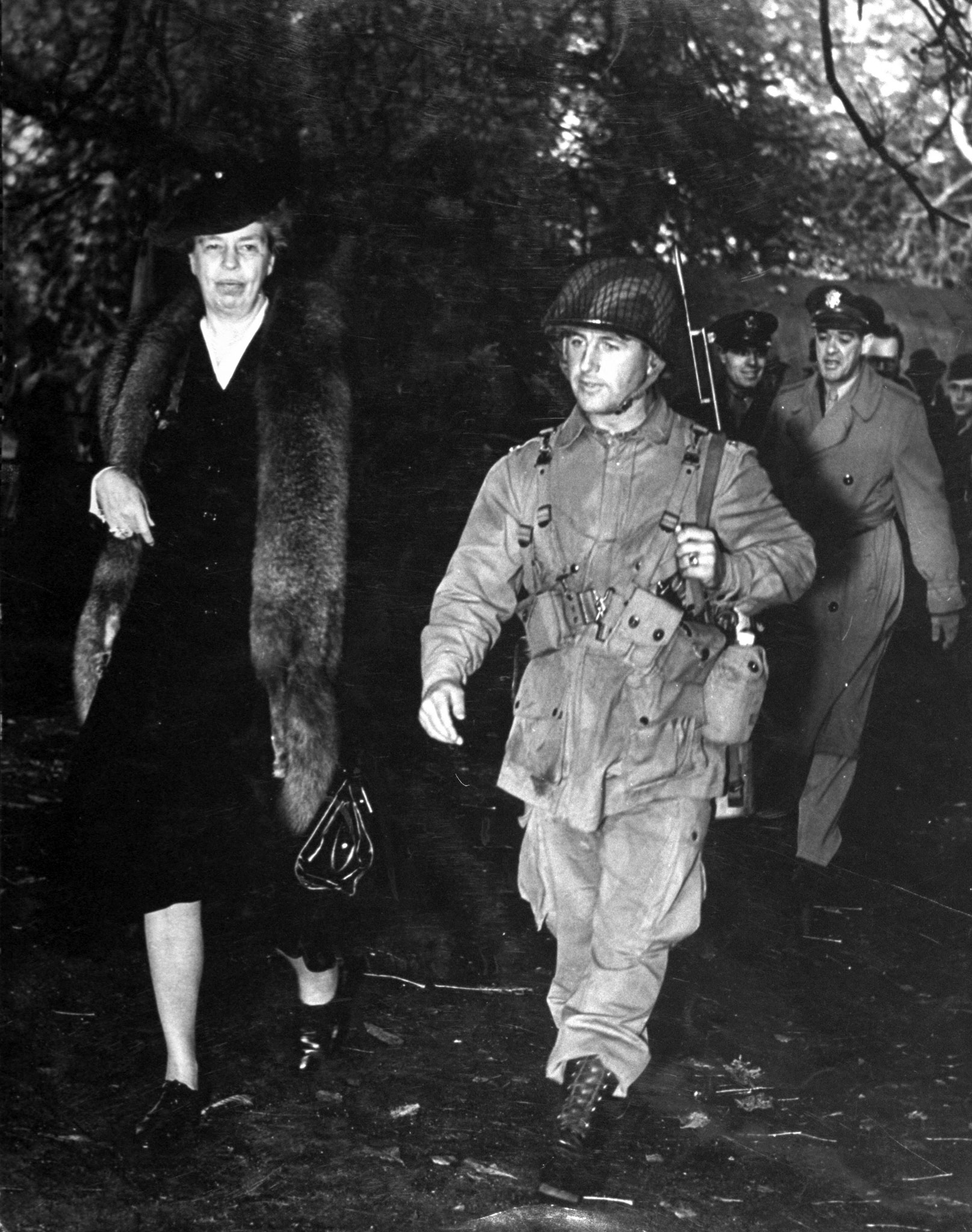 Eleanor Roosevelt walking and talking with the commanding officer of a group of American paratroopers, 1942.