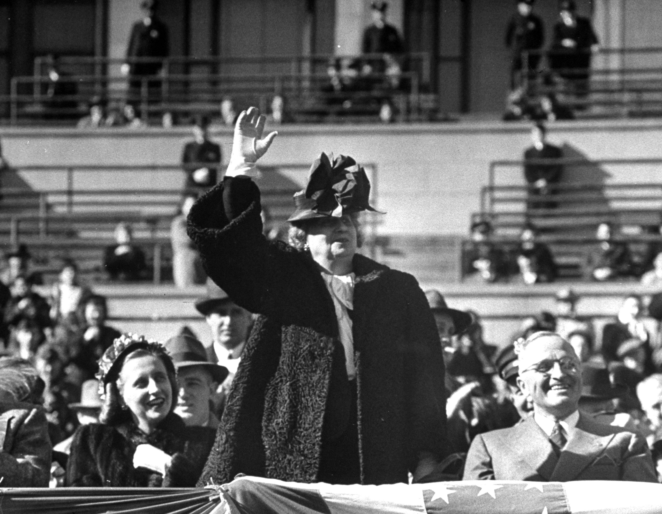 Bess Truman waving to crowd as her husband, President Harry S. Truman, and daugther Margaret look on during Army Day, 1946.