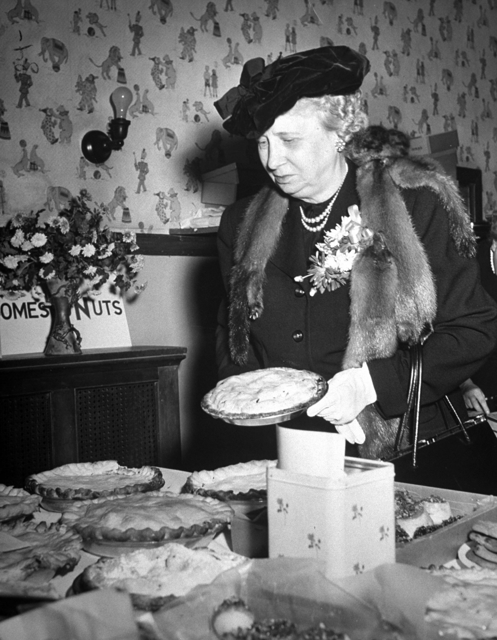 Bess Truman looking over a table full of baked goods, 1949.