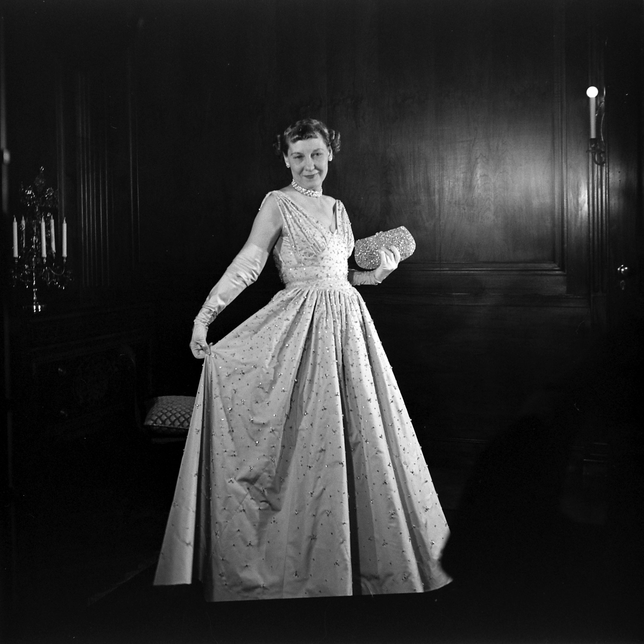 Mamie Eisenhower posing in her inaugural ball gown with a jeweled purse encrusted with 3,456 pink pearls, 1953.