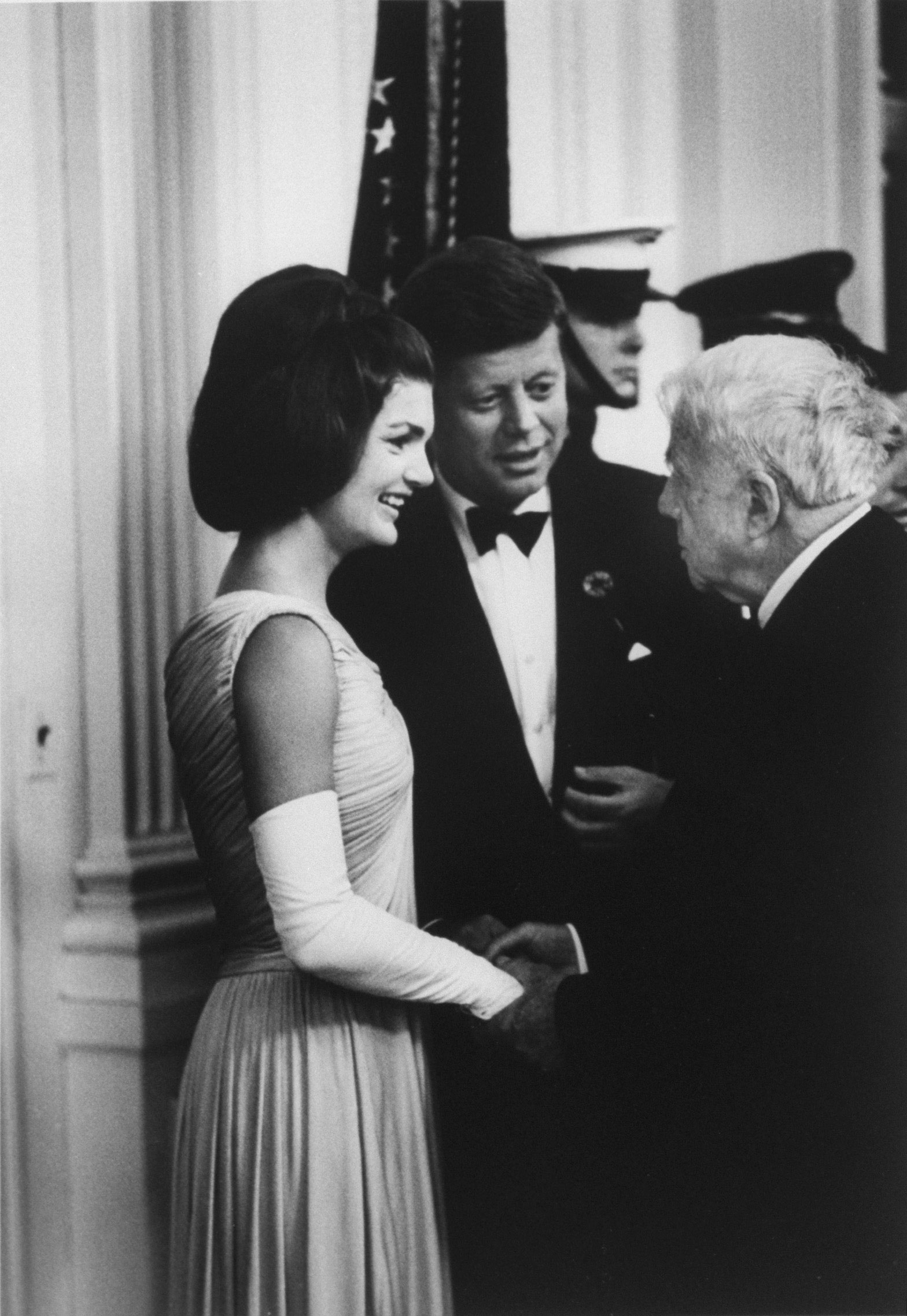 President John F. Kennedy and his wife Jackie chatting with poet Robert Frost at a party for Nobel Prize winners at the White House, 1962.