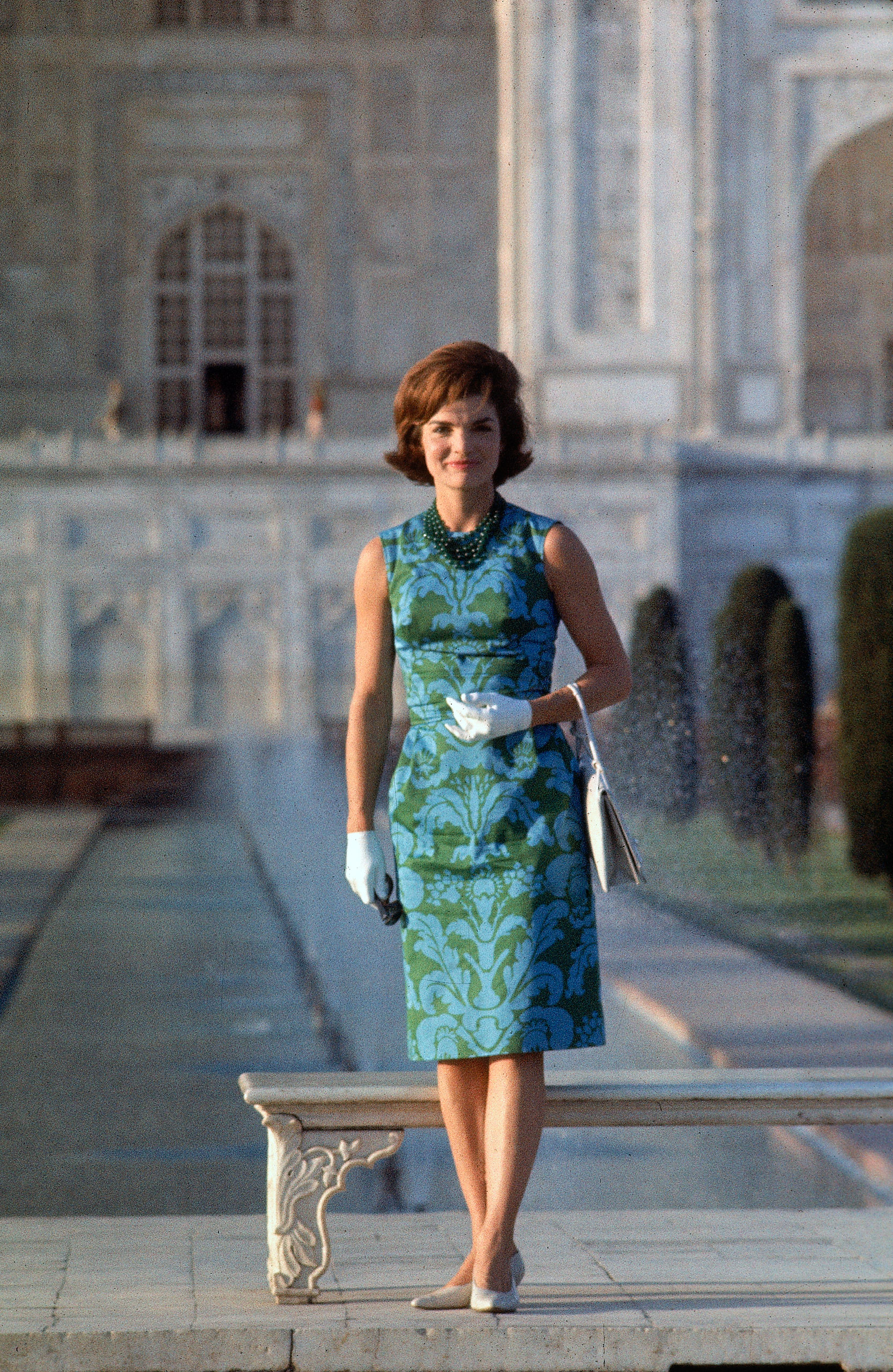 First Lady Jackie Kennedy standing on the grounds of the Taj Mahal during visit to India, 1962.