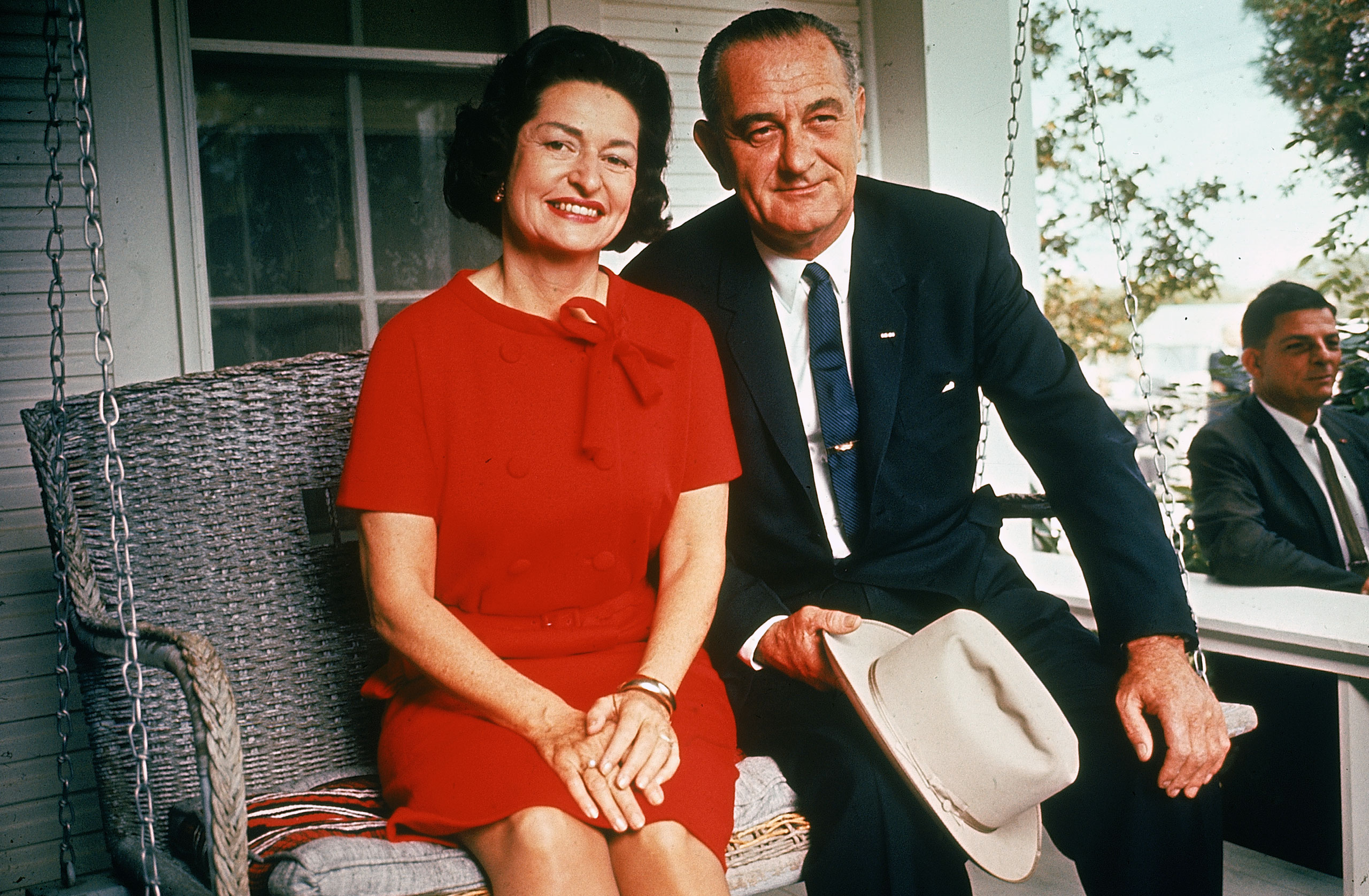 President Lyndon Johnson sitting on porch swing with wife Claudia (Lady Bird) on the morning following his landslide election win, 1964.