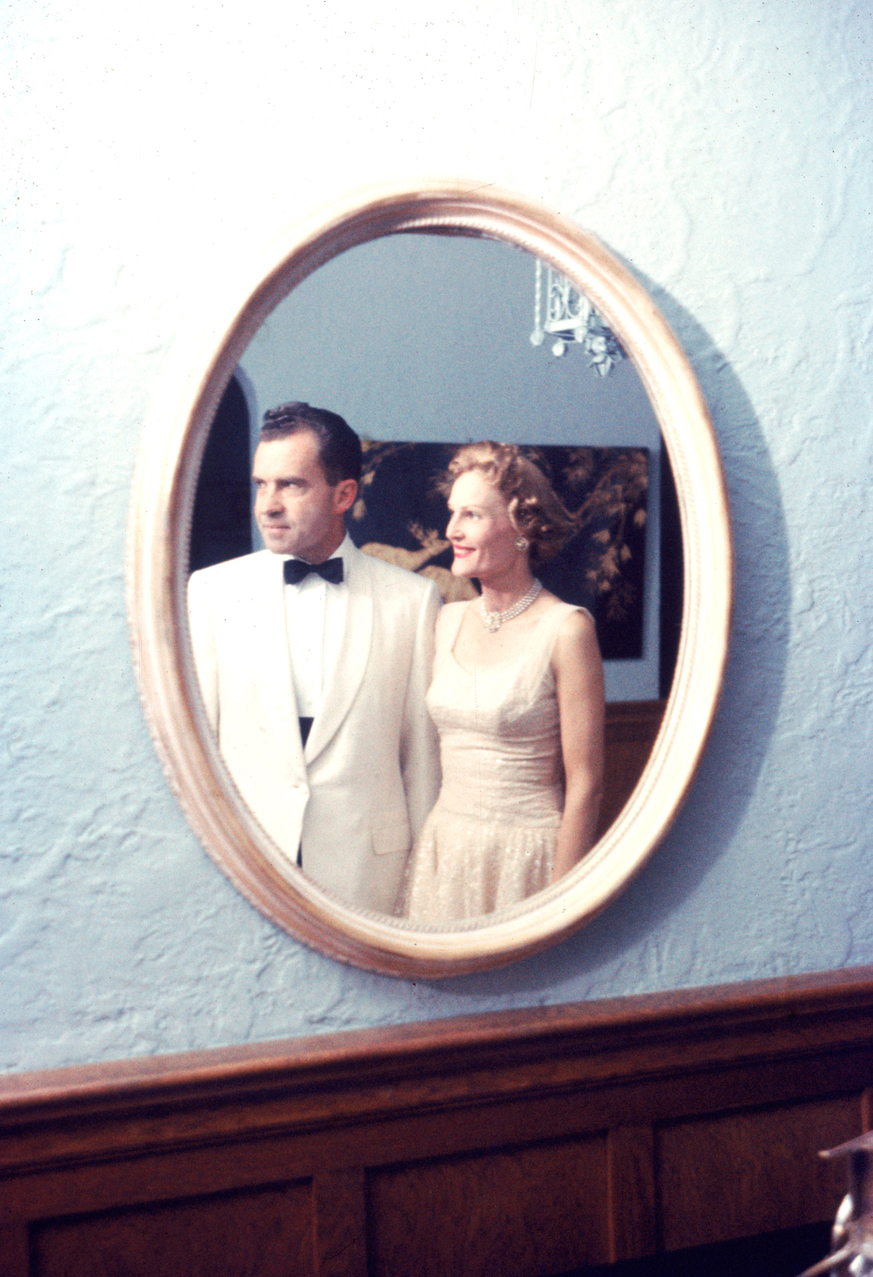 Vice President Richard Nixon and his wife Pat in formal dress reflected in oval mirror, 1958.