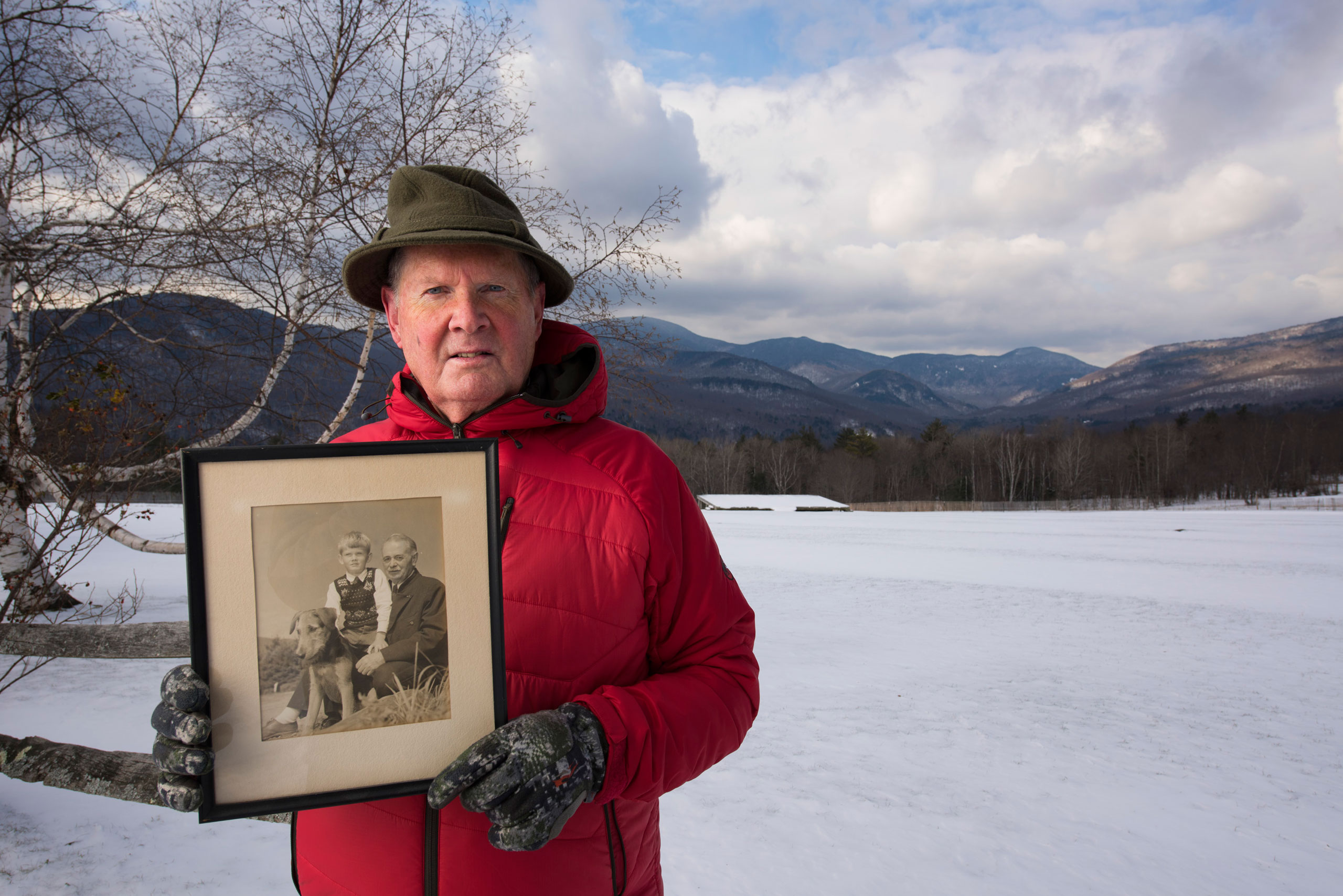 Portrait of Johannes von Trapp at the Trapp Family Lodge, alongside a field where music is performed in warmer weather. He is holding a portrait of his father and himself.