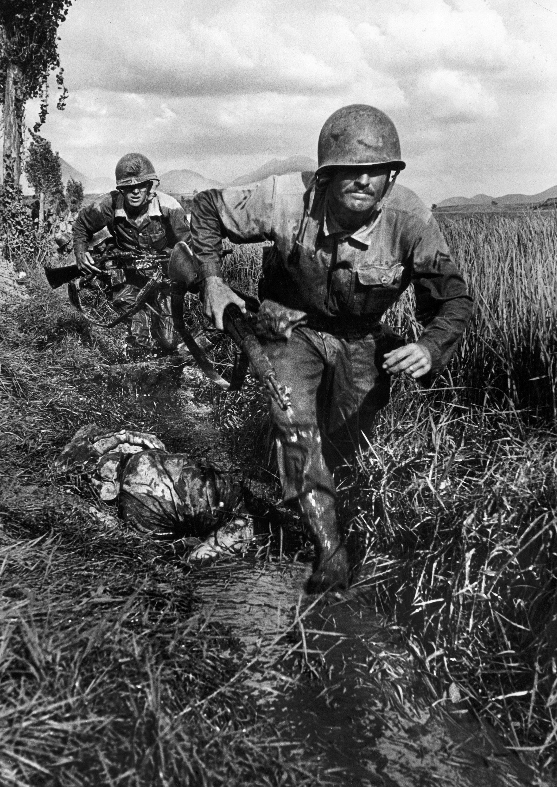 American Marines race past a dead enemy soldier in Korea, September 1950.