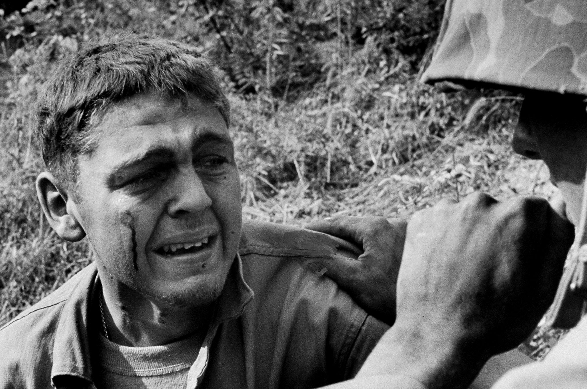 Wounded when a mine blew up his Jeep, an ambulance driver sobs by the side of the road after learning that a friend was killed in the blast, Korea 1950.