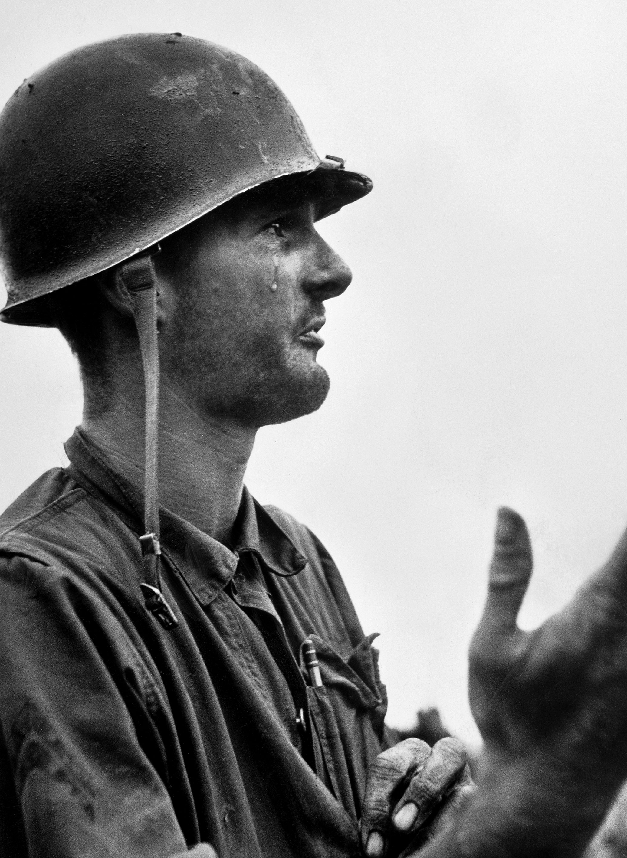 """""""Corporal Leonard Hayworth ... shows his utter frustration as he has crawled back from his position only to learn that the ammo is gone. Coda: At the last moment, supplies arrived and the men were able to hold their position."""" — From David Douglas Duncan's 1951 book, <em>This Is War!</em>"""