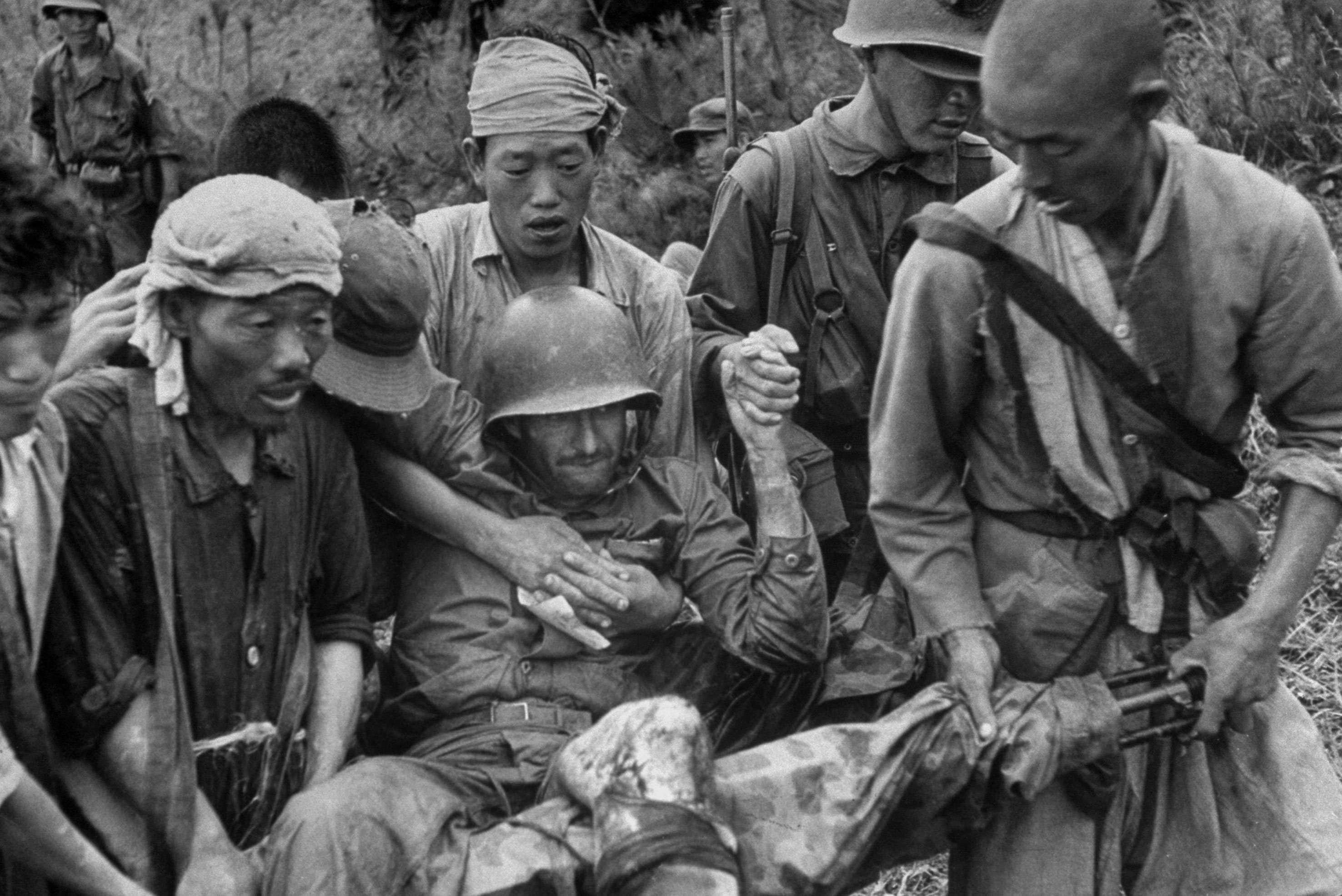 A wounded American Marine is carried on stretcher improvised from a machine gun, Korea 1950.